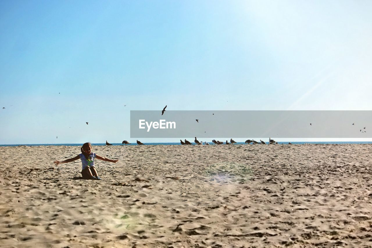 Girl With Arms Outstretched Sitting At Beach Against Clear Sky During Sunny Day