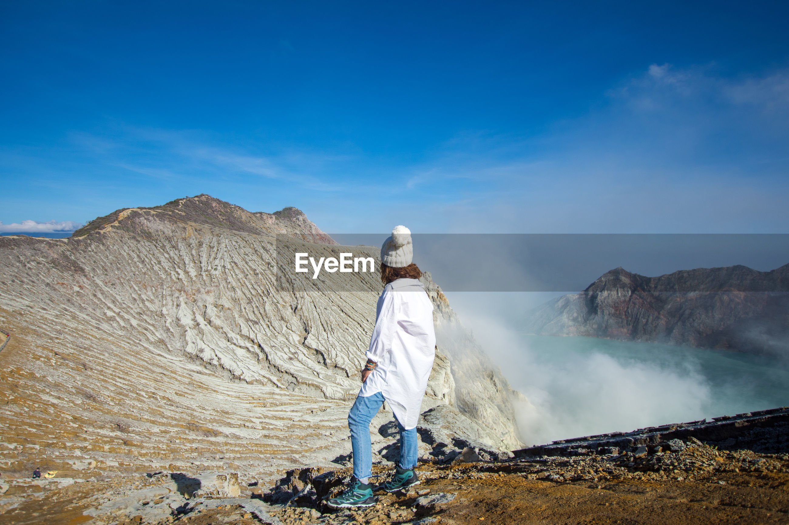 Woman looking at view of hot spring standing on mountain against sky