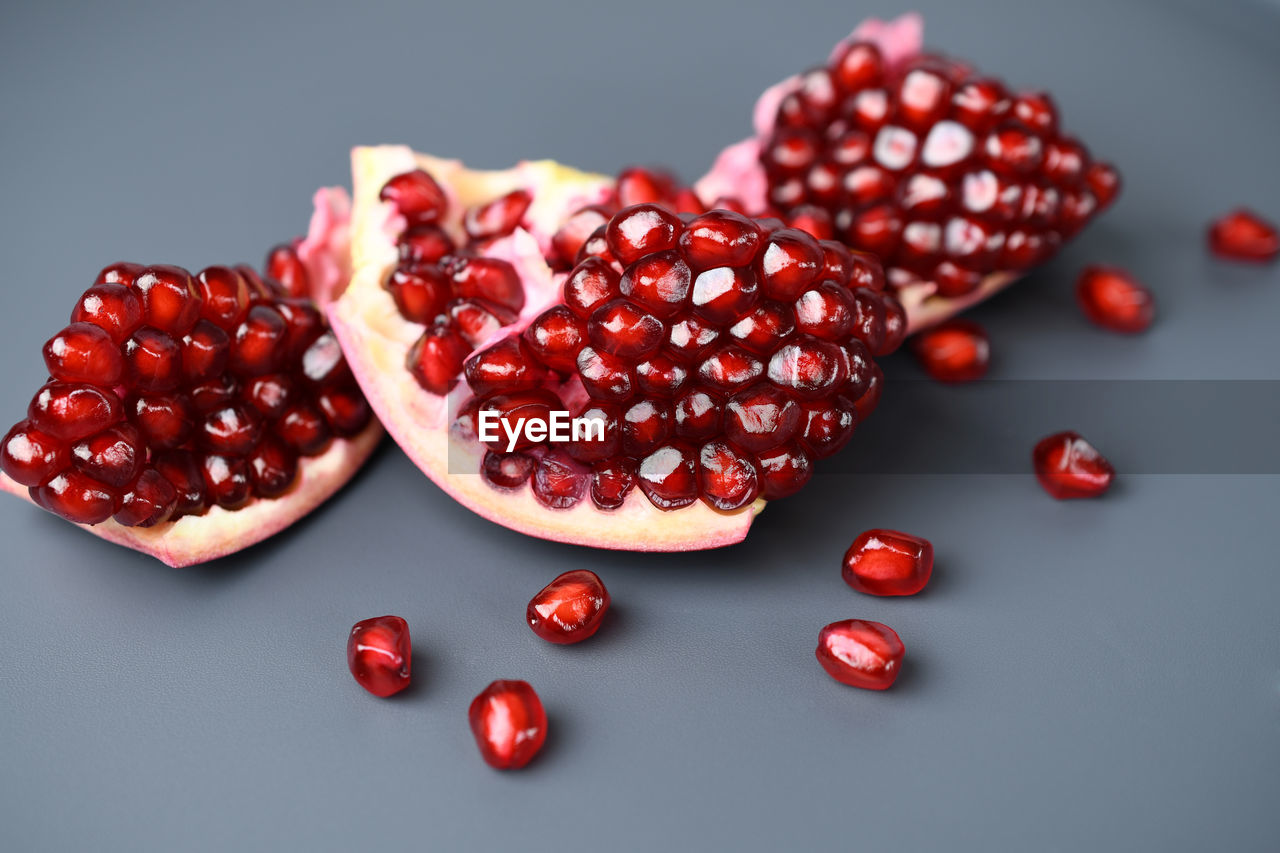 red, fruit, pomegranate seed, pomegranate, food and drink, wellbeing, food, still life, freshness, seed, healthy eating, indoors, no people, studio shot, close-up, table, high angle view, focus on foreground, berry fruit, large group of objects, red currant, temptation