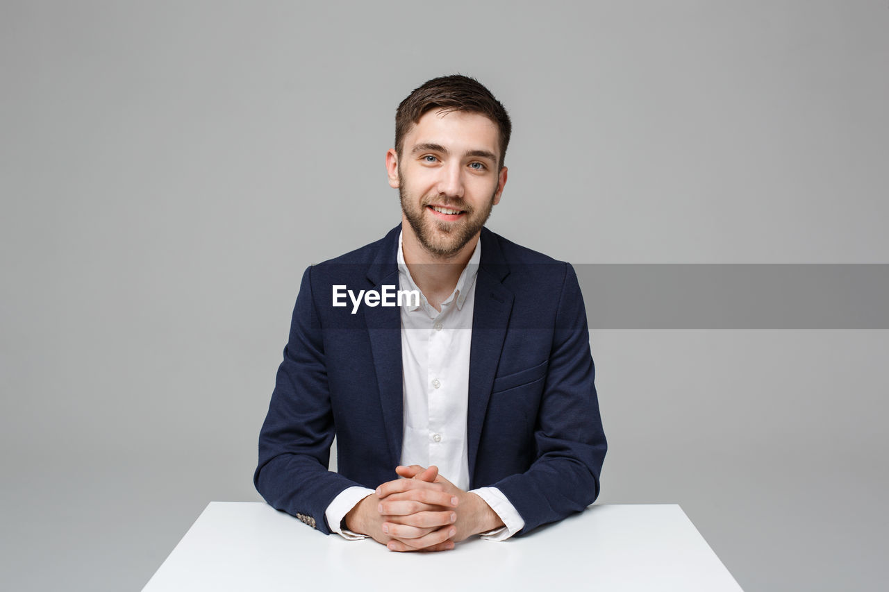 Portrait of young businessman sitting against gray background