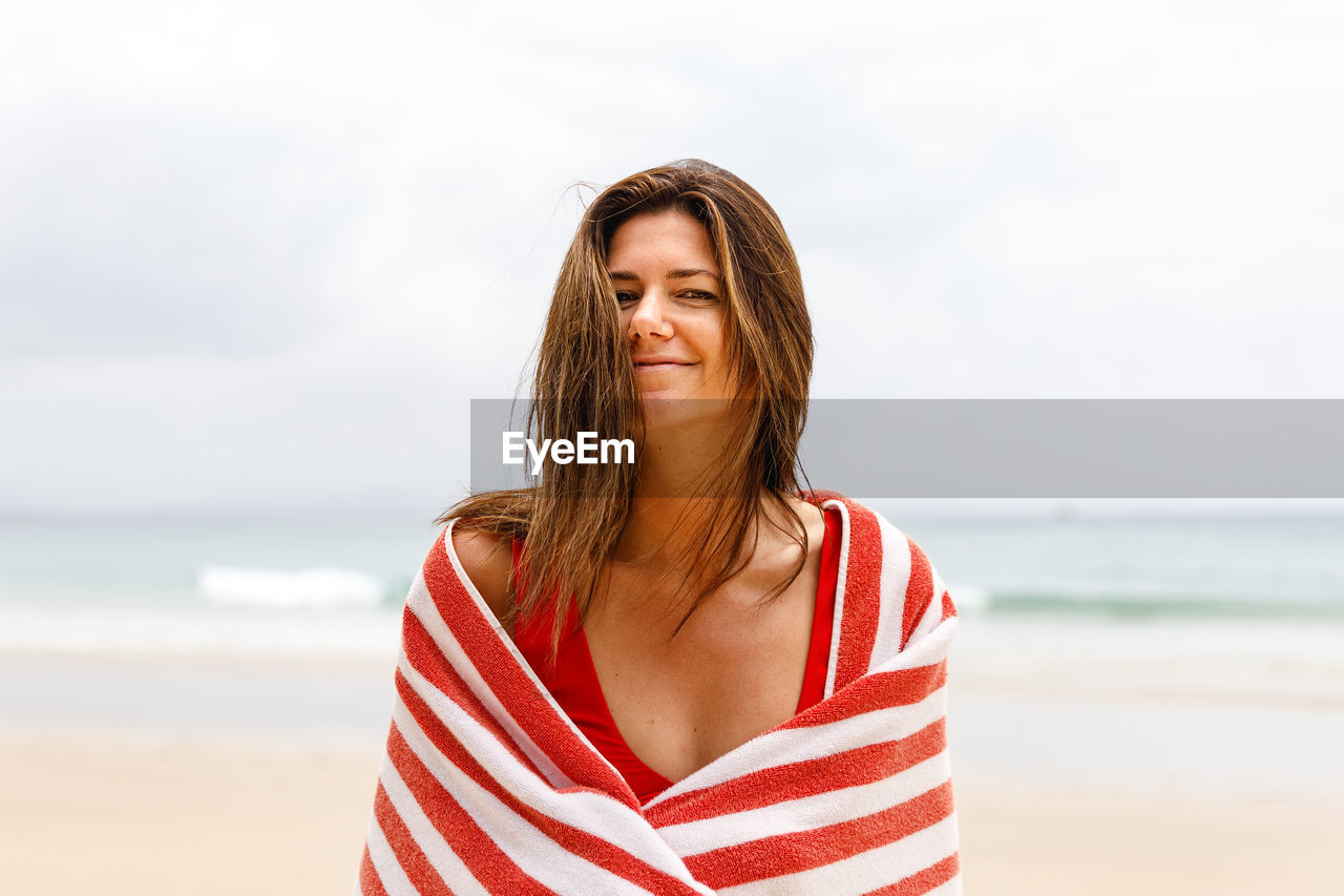 sea, beach, water, one person, land, smiling, beauty, leisure activity, real people, young women, young adult, portrait, beautiful woman, sky, lifestyles, front view, casual clothing, standing, hairstyle, hair, outdoors