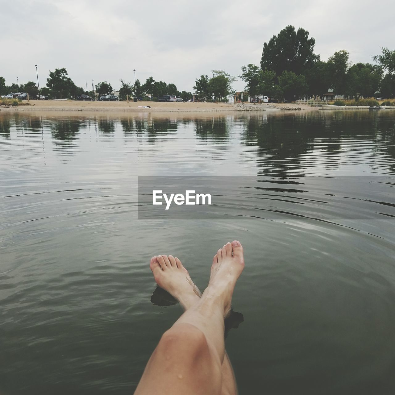 Low section of man relaxing in lake