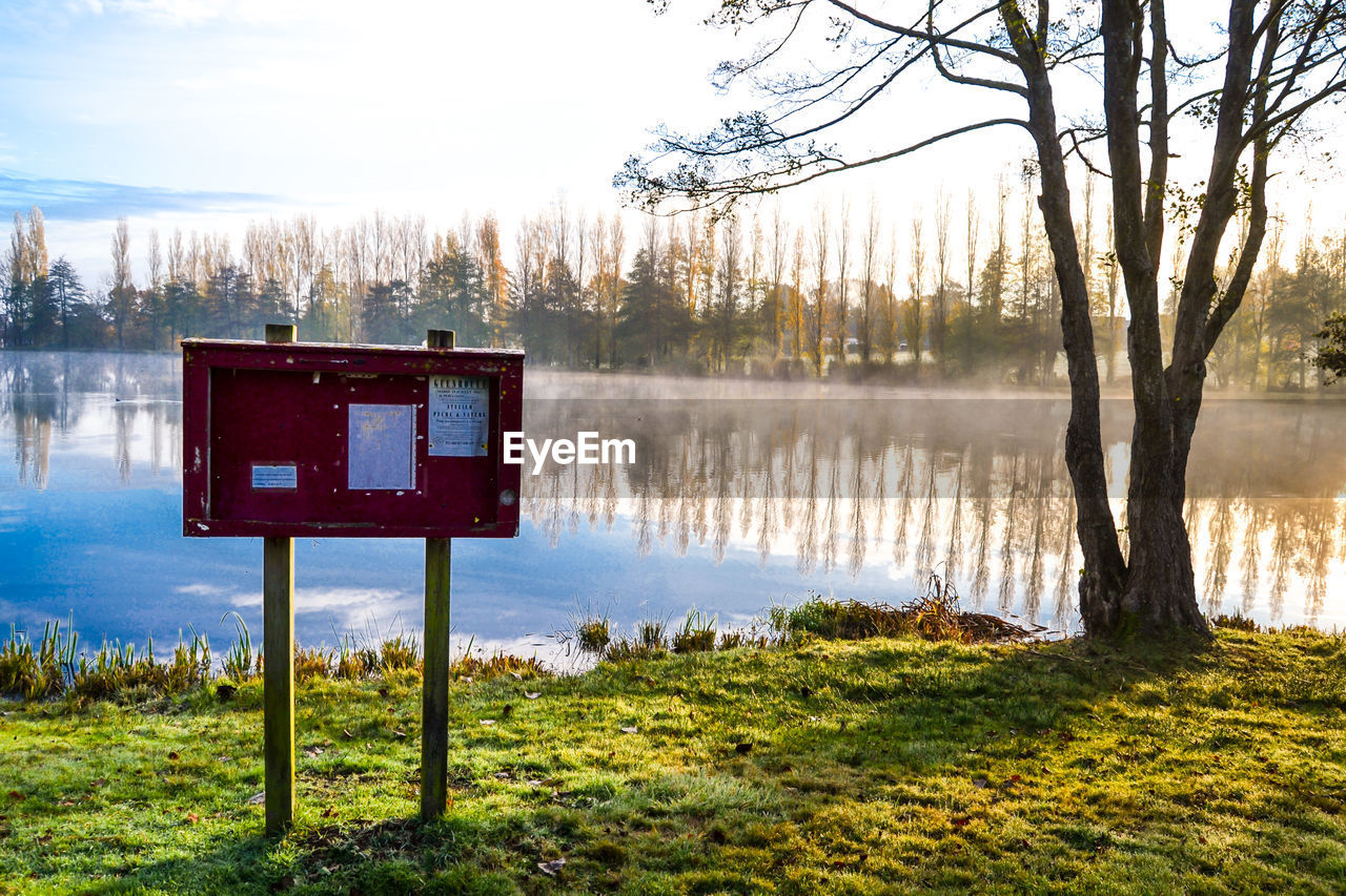 Information Sign On Lake Against Sky
