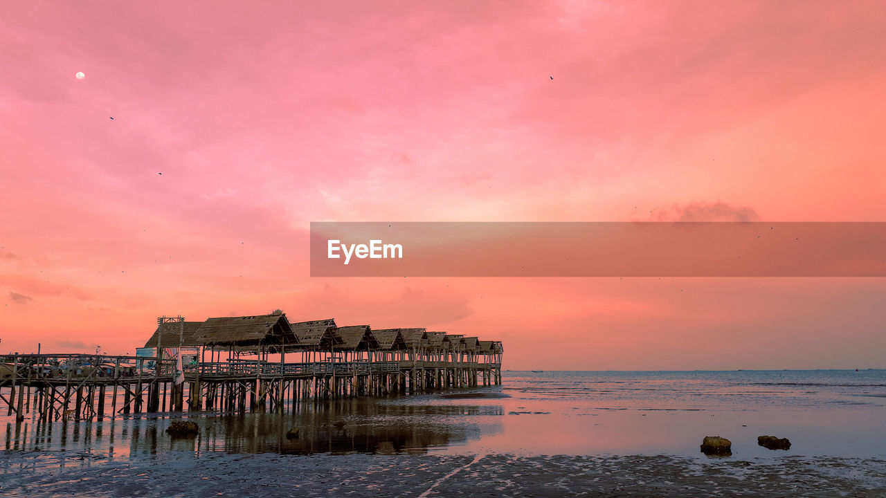 water, sky, sea, sunset, built structure, architecture, beach, scenics - nature, beauty in nature, nature, horizon over water, cloud - sky, horizon, building exterior, land, orange color, tranquility, no people, building, purple, wooden post