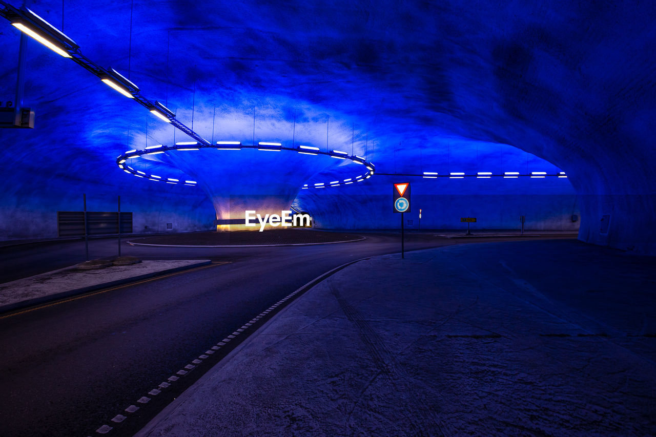 illuminated, transportation, night, the way forward, direction, architecture, lighting equipment, road, no people, cloud - sky, light, dusk, blue, sky, public transportation, built structure, city, long exposure, motion, nature, outdoors