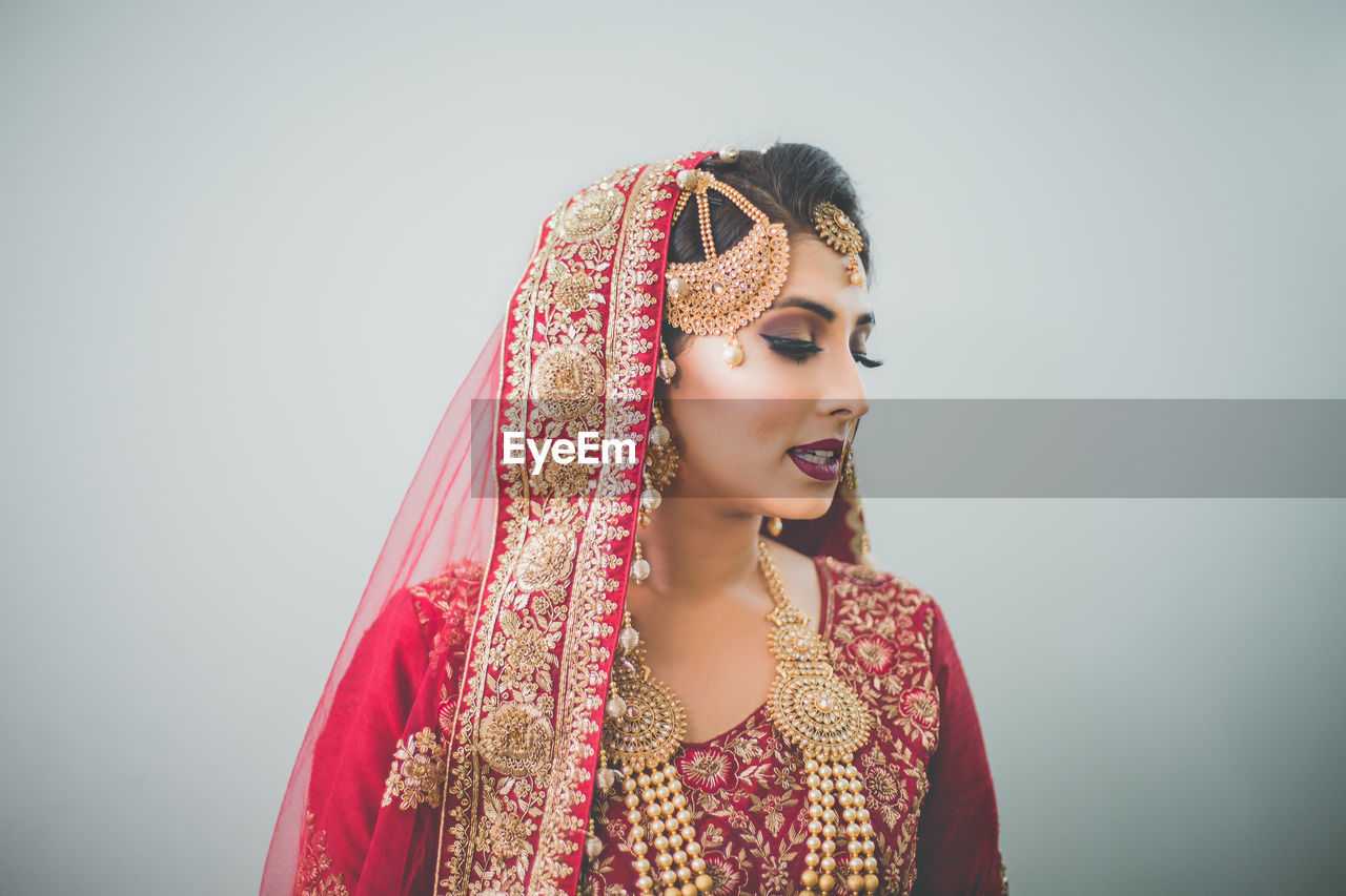 Beautiful Bride In Red Traditional Clothing Against White Background