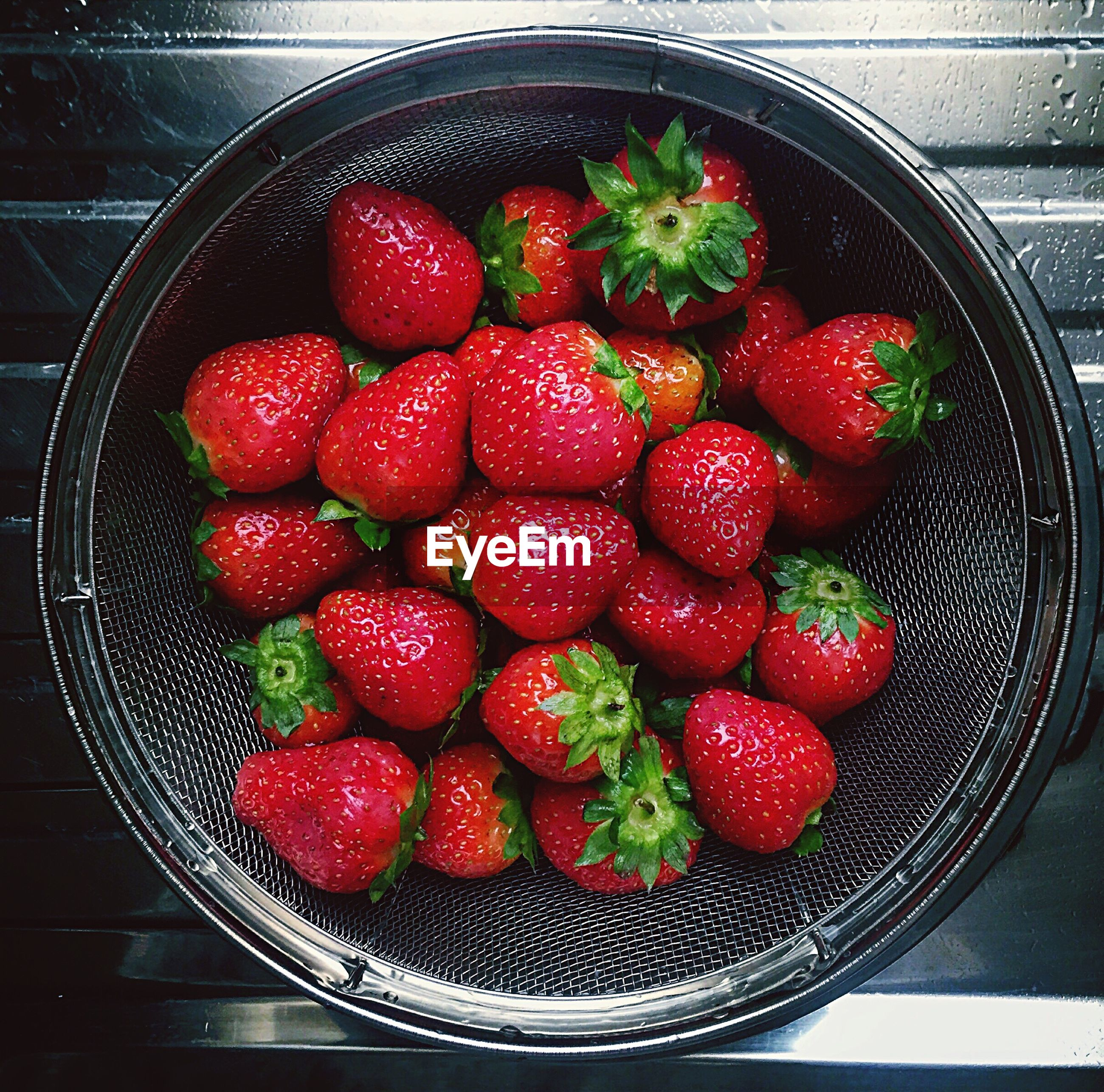 Directly above shot of strawberries in colander on table