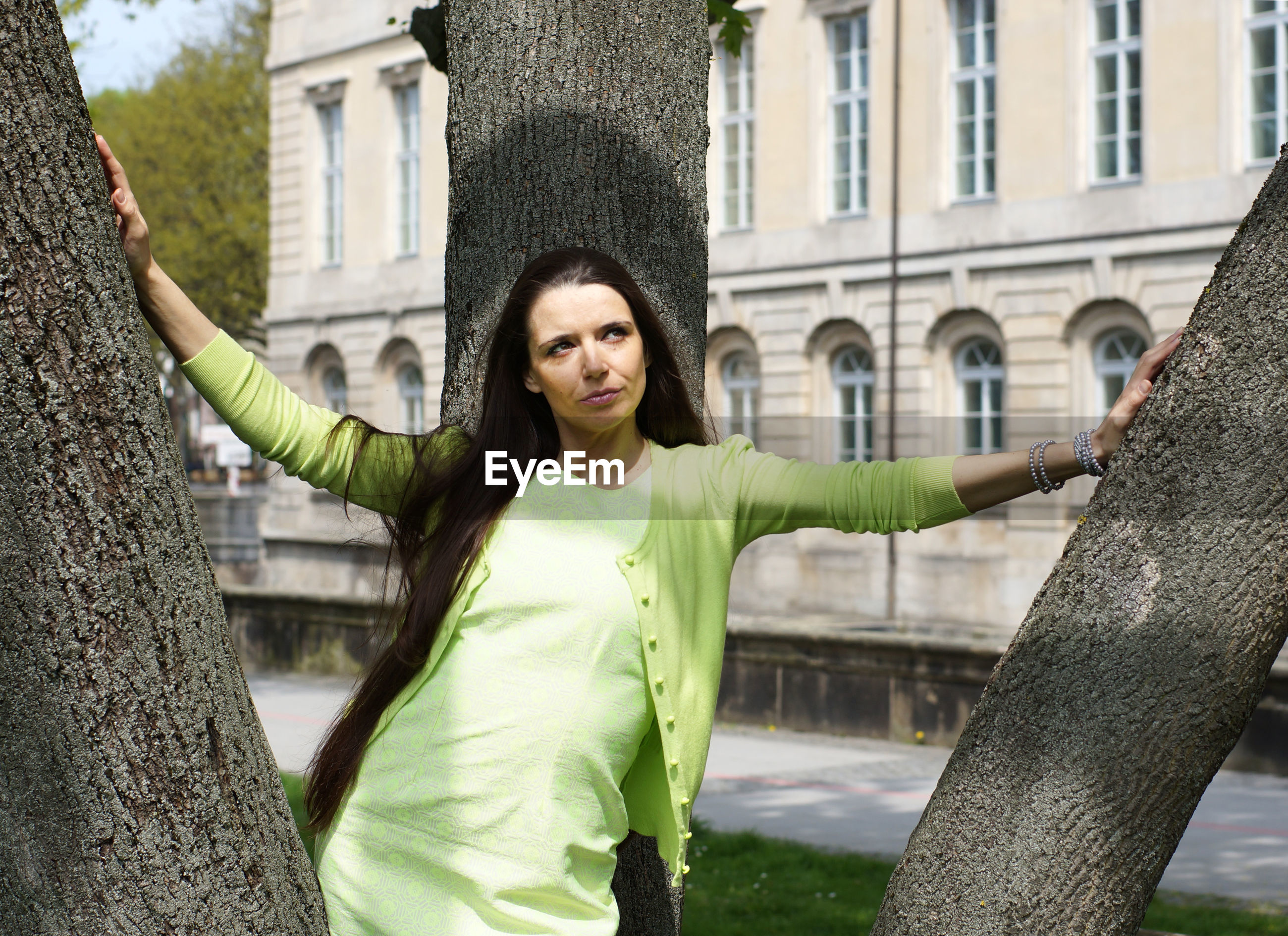 Woman looking away while standing by tree in city