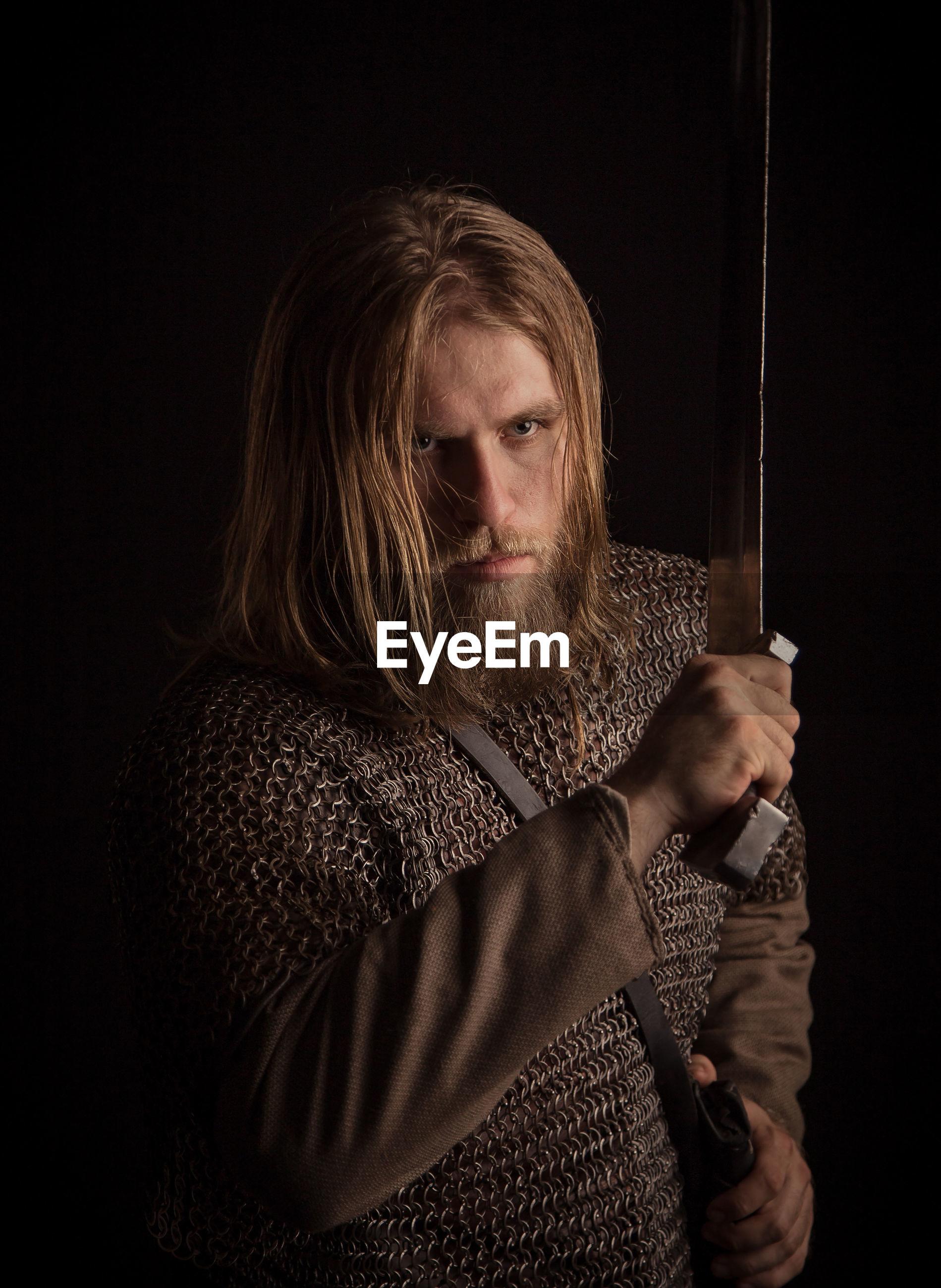 Viking holding sword against black background