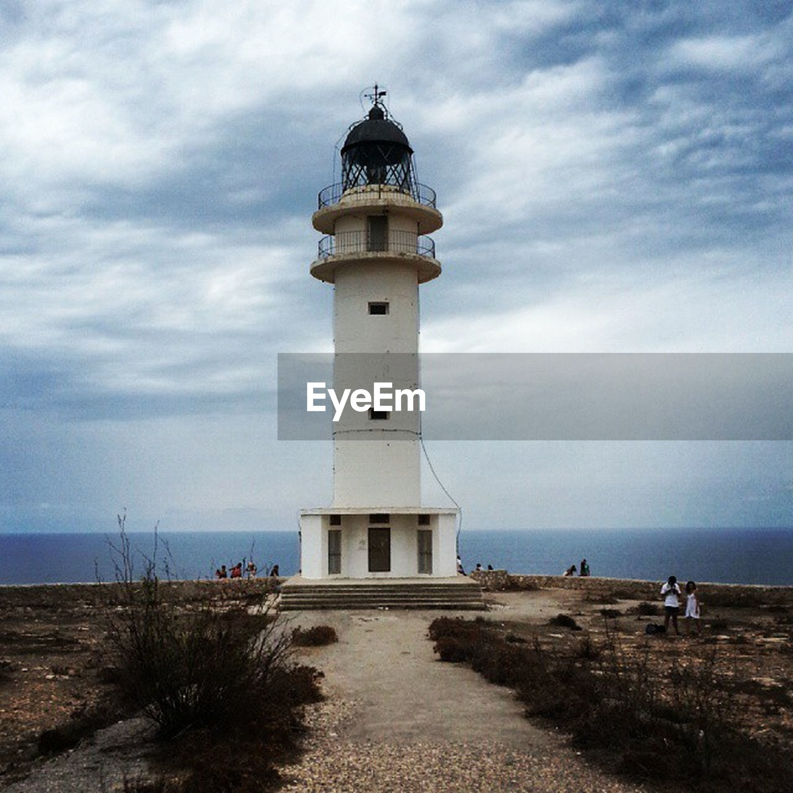 lighthouse, sea, sky, horizon over water, beach, guidance, water, built structure, architecture, cloud - sky, protection, building exterior, safety, sand, direction, shore, cloud, security, cloudy, tranquility