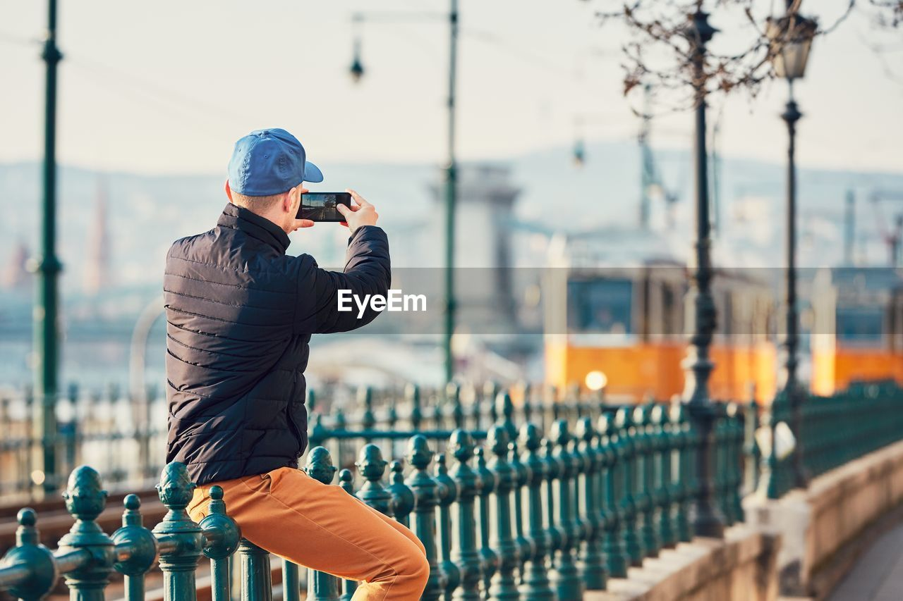 Rear View Of Man Photographing While Sitting On Railing