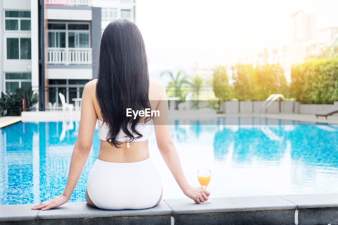 Rear view of woman relaxing at poolside