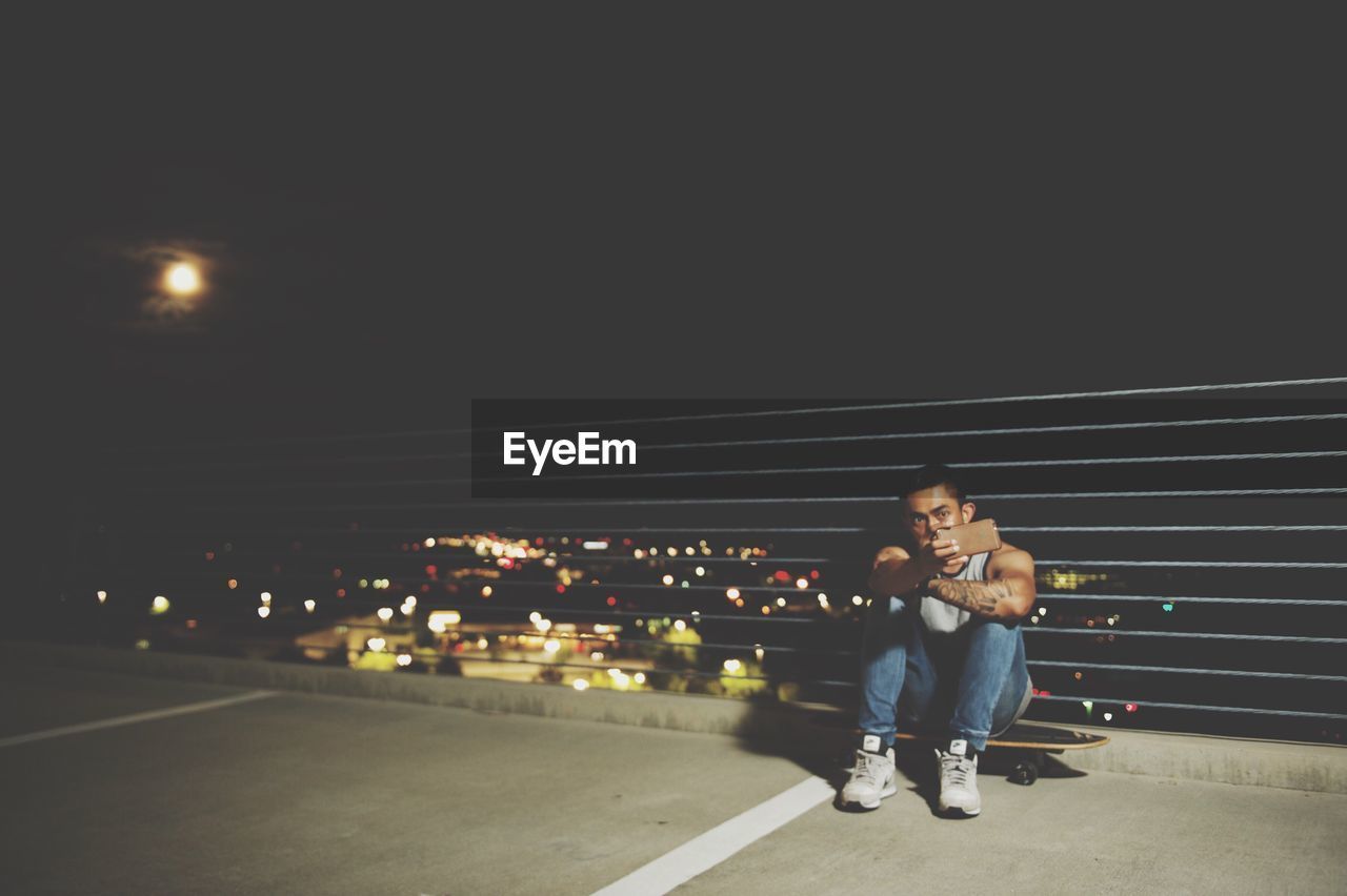 real people, two people, full length, casual clothing, illuminated, night, outdoors, togetherness, lifestyles, looking at camera, boys, road, bonding, childhood, young adult, portrait, architecture, city, sky, people