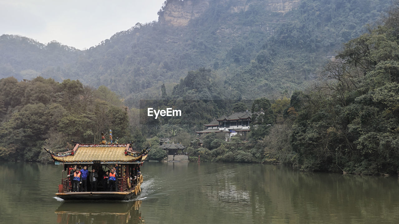 tree, water, mountain, group of people, waterfront, plant, nature, transportation, real people, built structure, architecture, river, day, beauty in nature, mode of transportation, travel, nautical vessel, scenics - nature, mountain range, outdoors