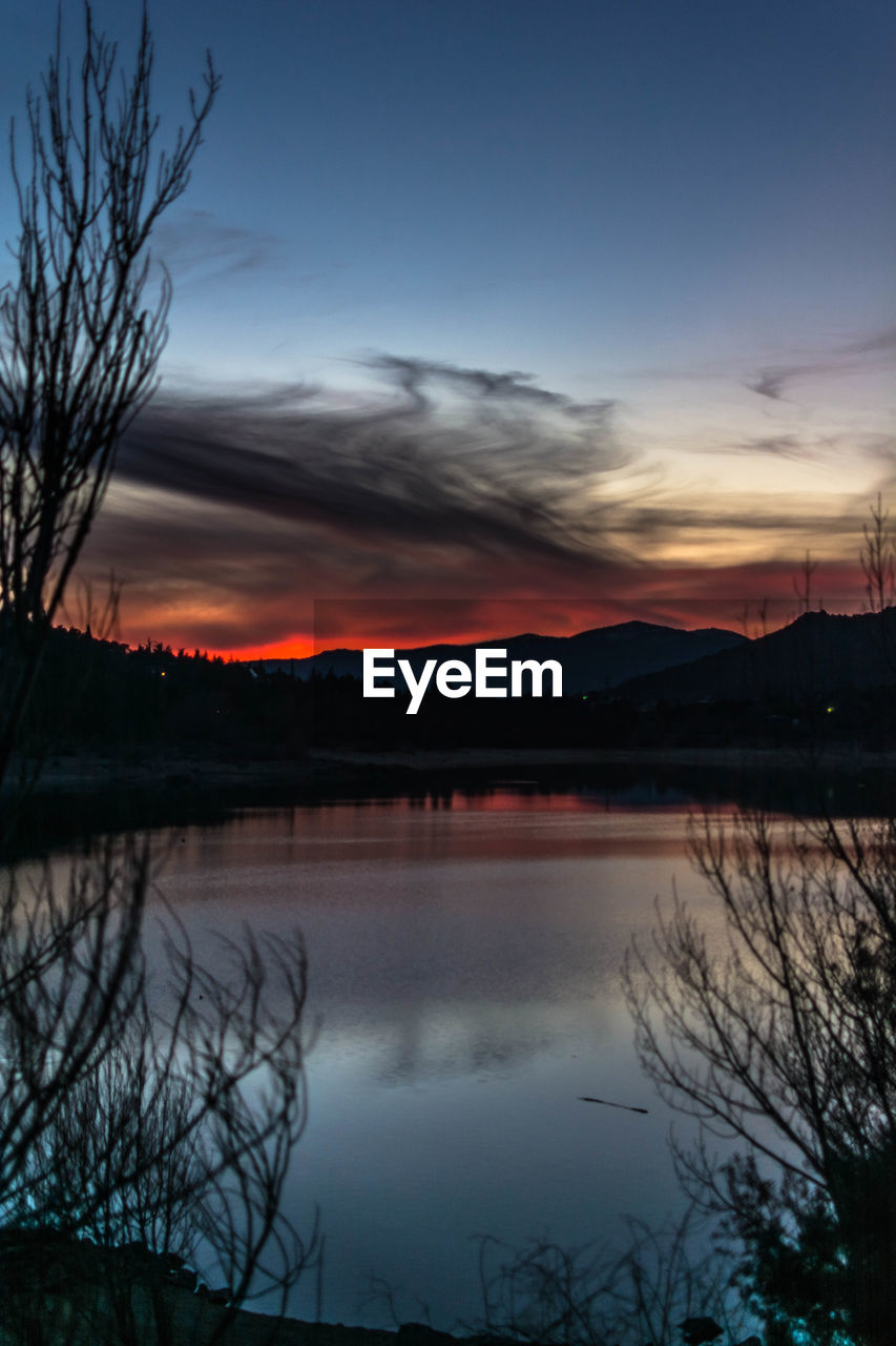 sunset, beauty in nature, reflection, scenics, nature, tranquil scene, sky, tranquility, water, lake, orange color, bare tree, no people, outdoors, idyllic, silhouette, tree, cloud - sky, mountain, day