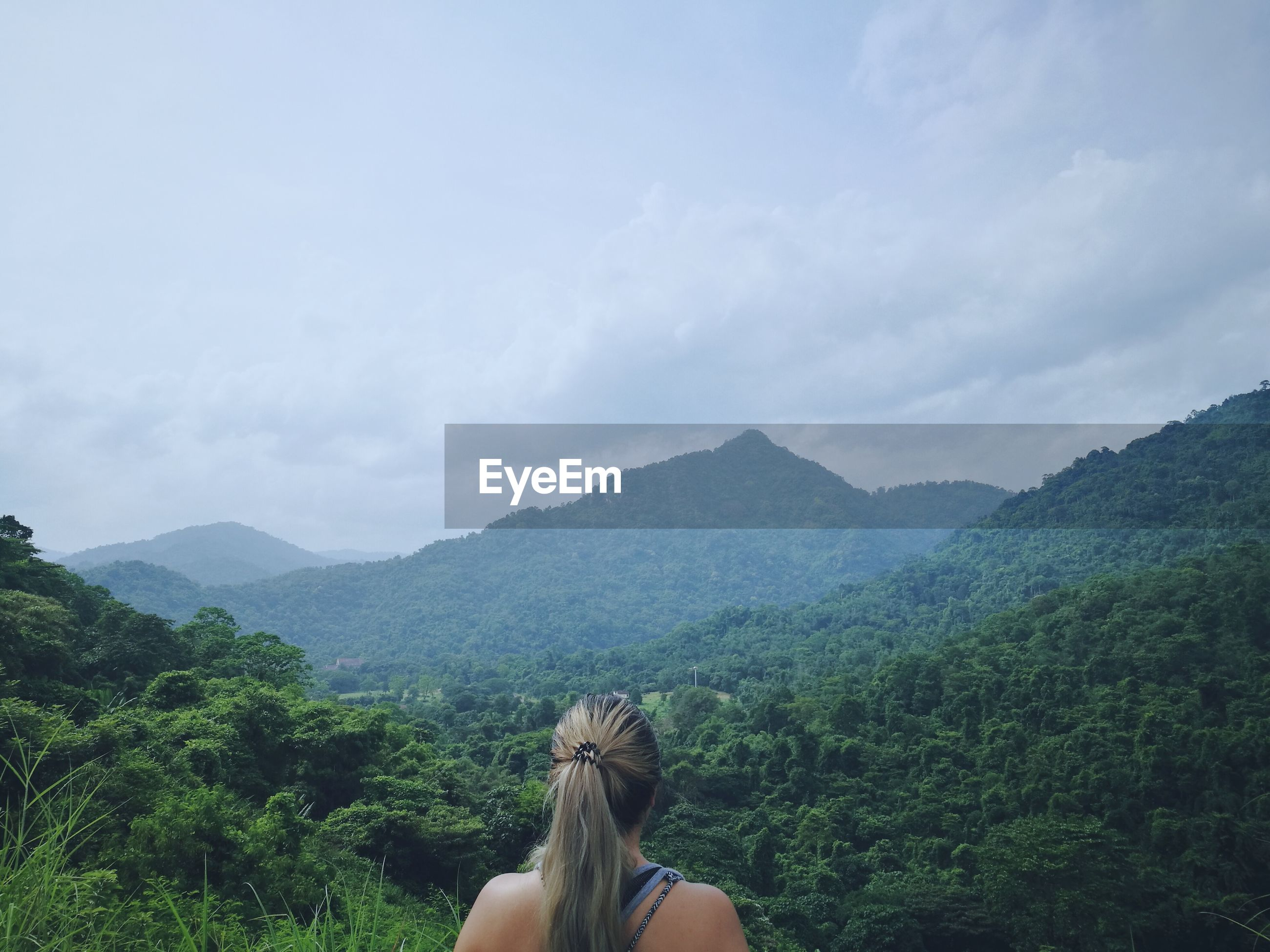 Rear view of woman looking at mountains while standing against cloudy sky