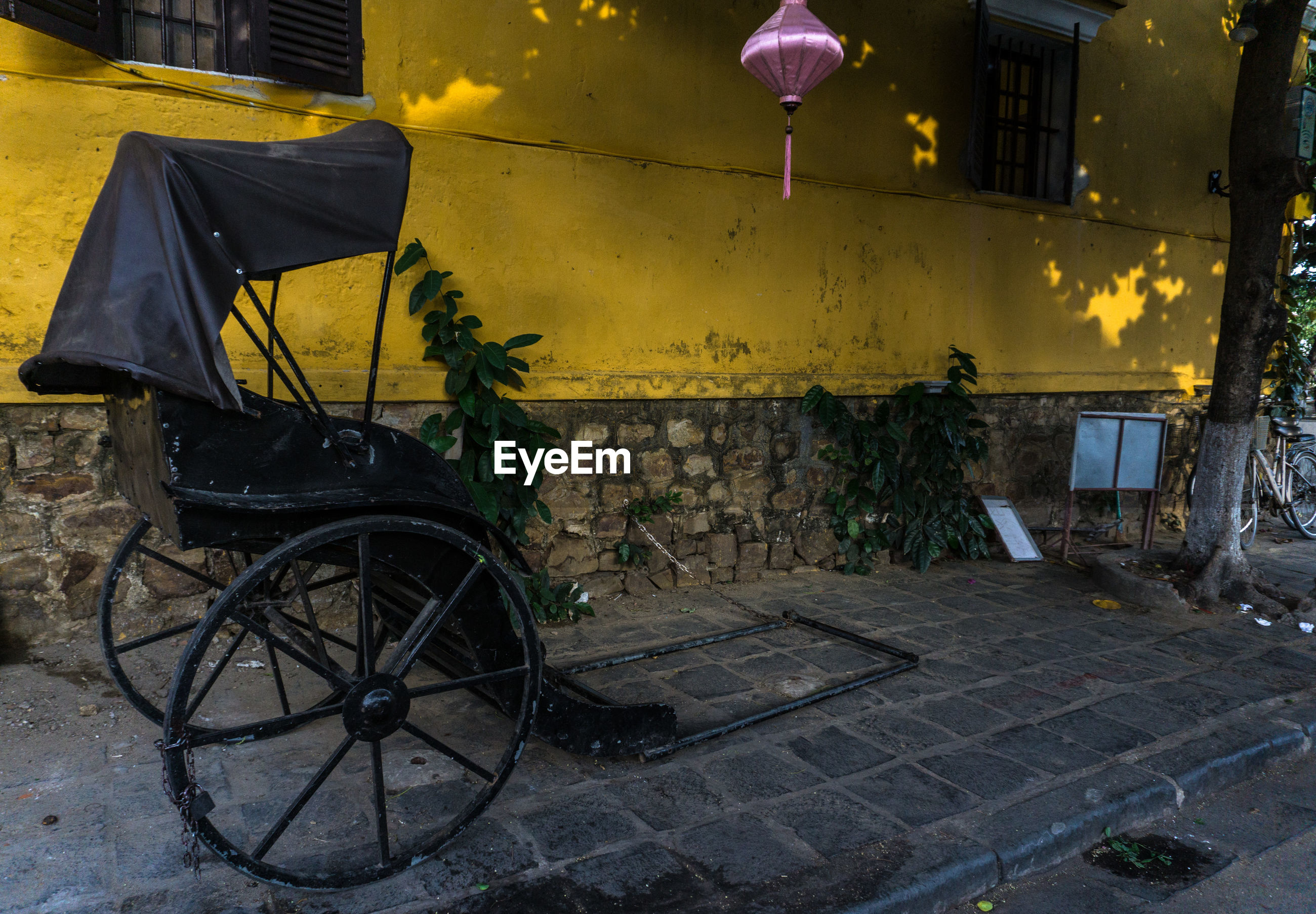 Old pedicab parked on footpath by building