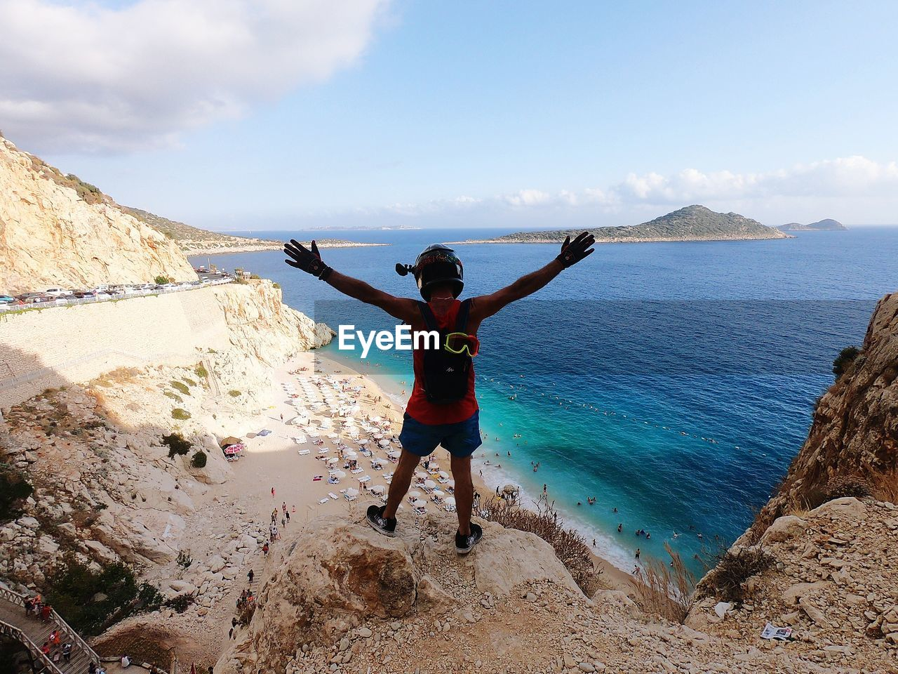 sky, leisure activity, real people, lifestyles, sea, one person, beauty in nature, water, full length, human arm, scenics - nature, standing, beach, nature, day, limb, casual clothing, rock, arms outstretched, arms raised, outdoors
