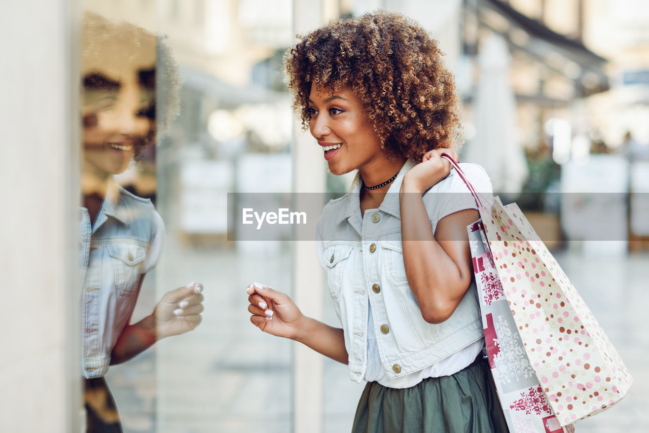 smiling, women, young adult, young women, happiness, emotion, focus on foreground, real people, standing, lifestyles, adult, portrait, casual clothing, curly hair, leisure activity, people, females, two people, looking at camera, hairstyle, beautiful woman, consumerism