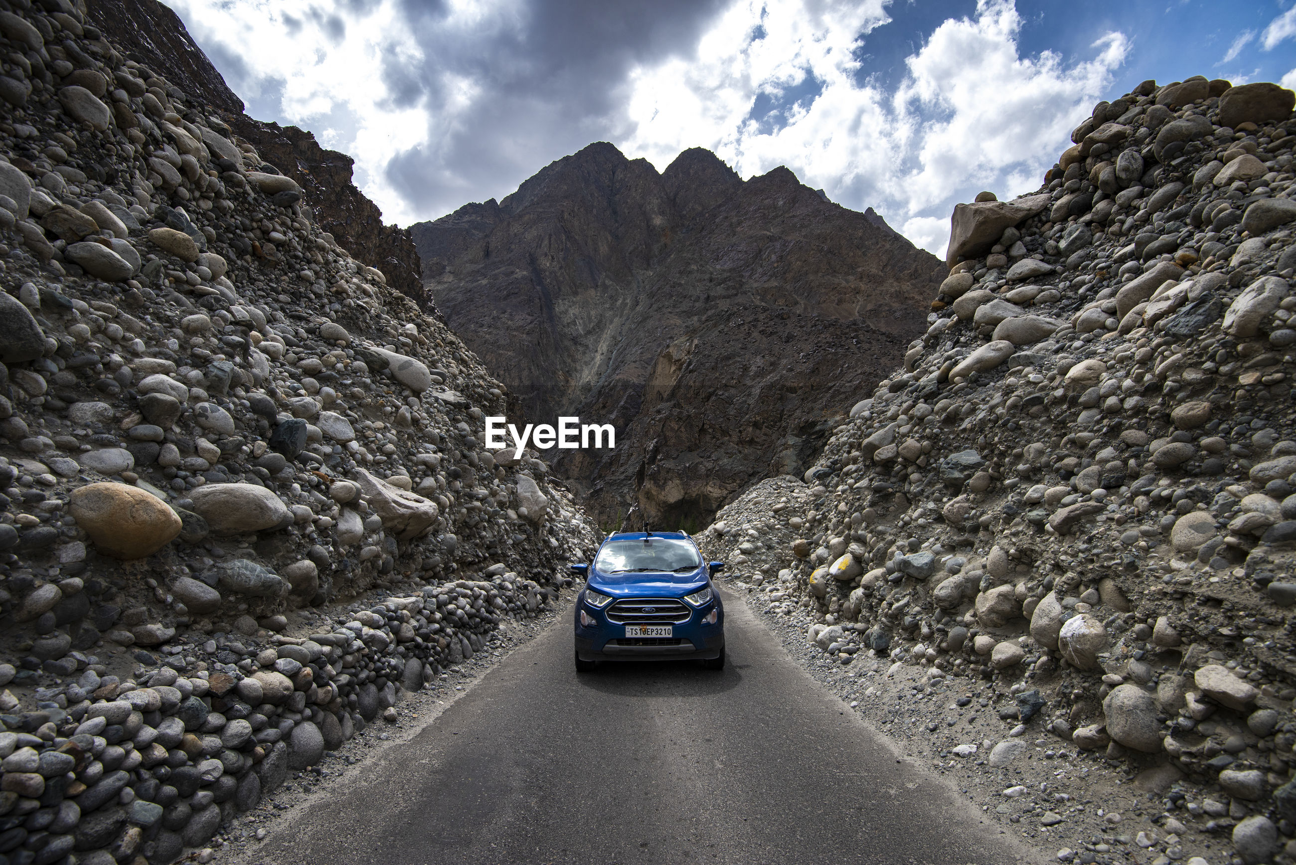 CARS ON ROAD AGAINST MOUNTAIN