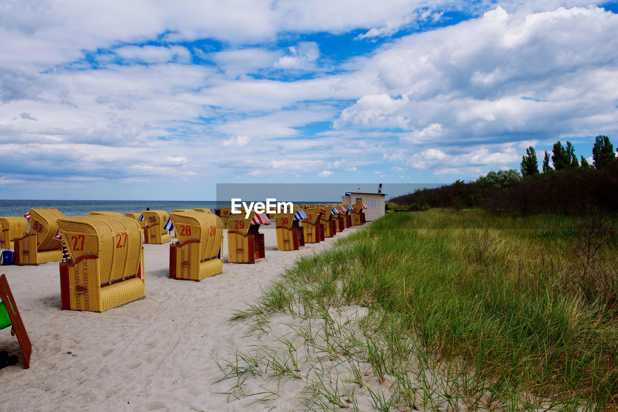 ROW OF HOODED BEACH CHAIRS ON SAND