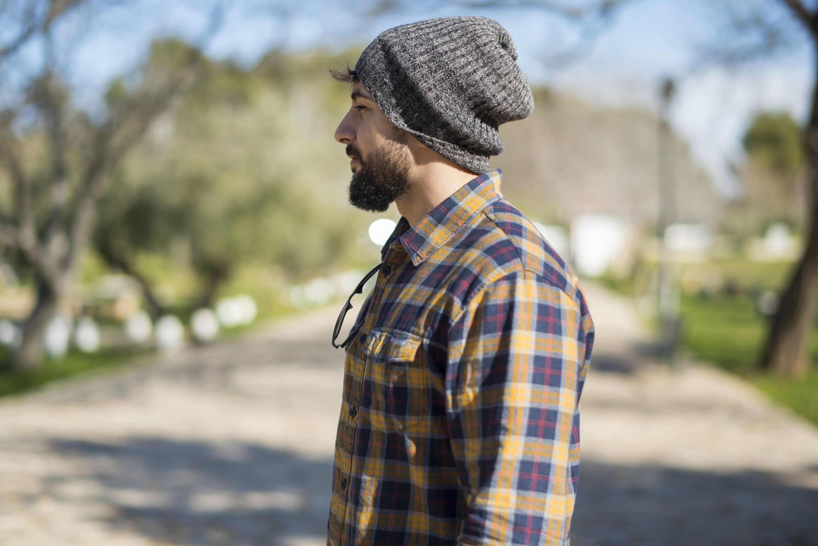 Side view of man wearing knit hat and shirt while looking away outdoors
