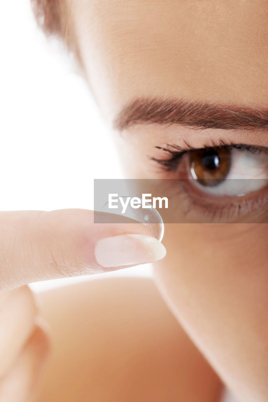 Close-up of woman applying contact lens in eye
