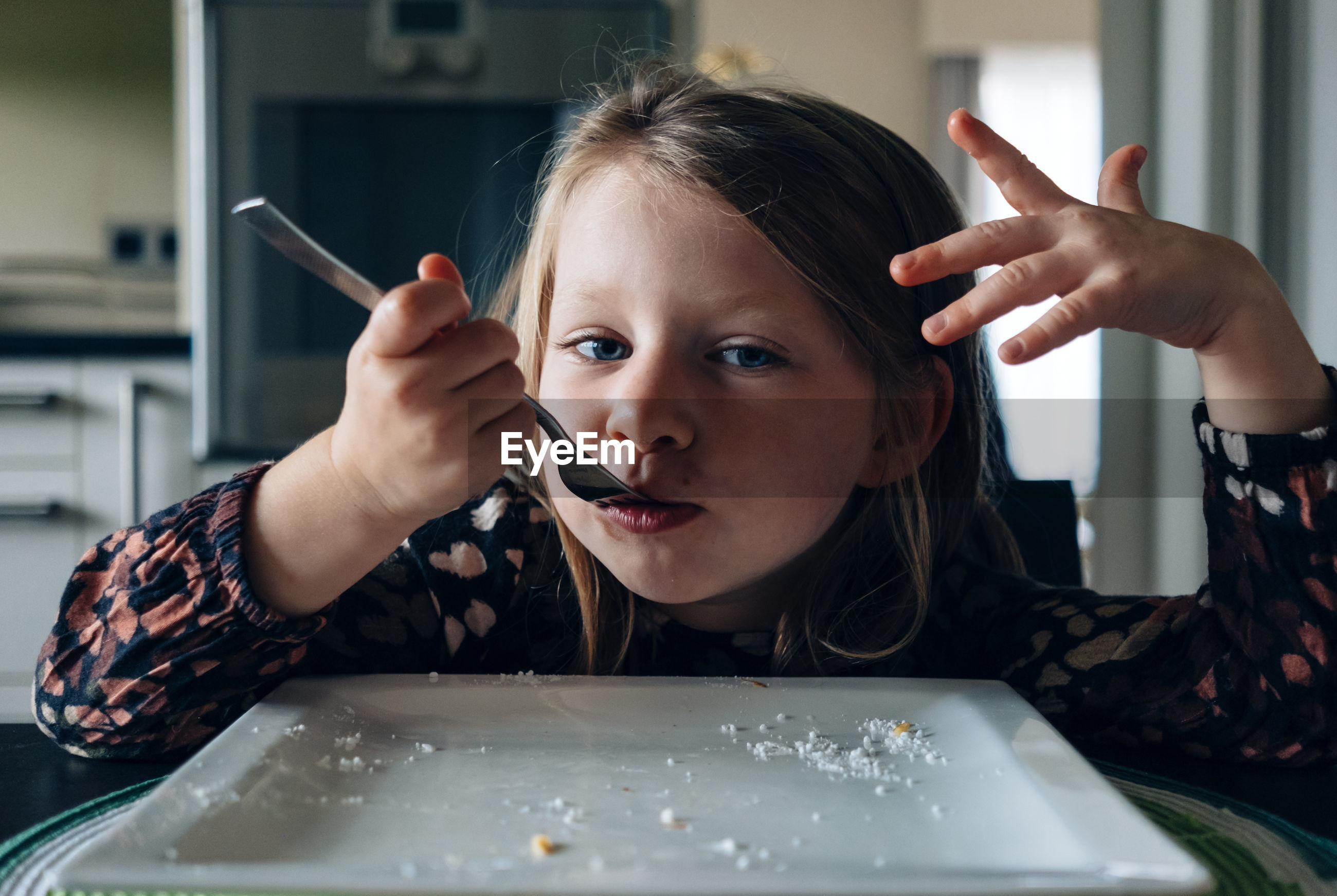 Portrait of girl eating food in plate at home