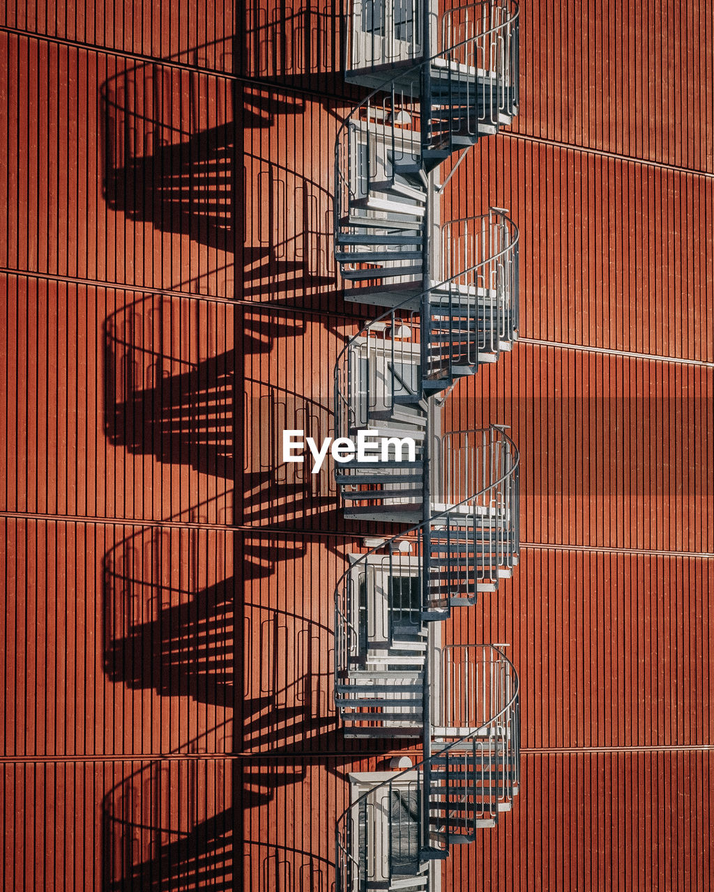 staircase, fire escape, steps and staircases, architecture, railing, pattern, no people, safety, metal, built structure, emergency exit, in a row, repetition, day, building exterior, shadow, spiral, security, backgrounds, accidents and disasters