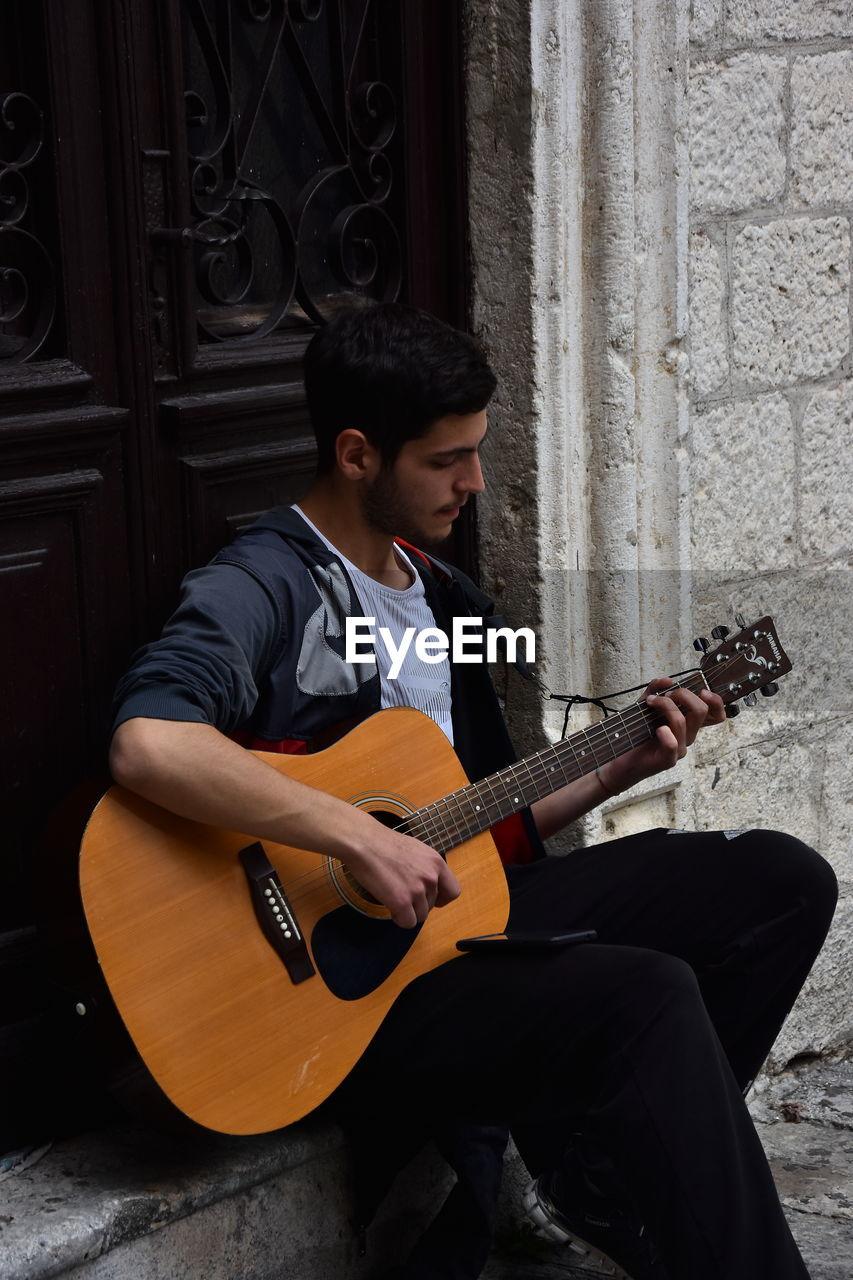 YOUNG MAN PLAYING GUITAR AT CAMERA