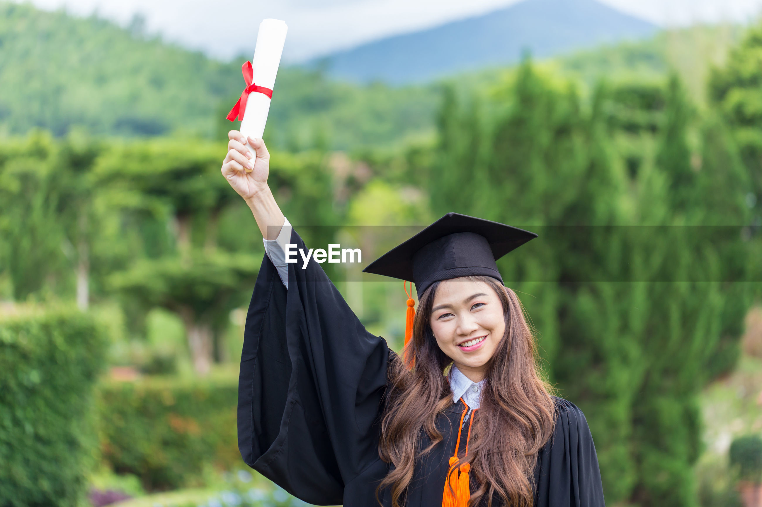Portrait of smiling woman in graduation gown holding certificate against trees