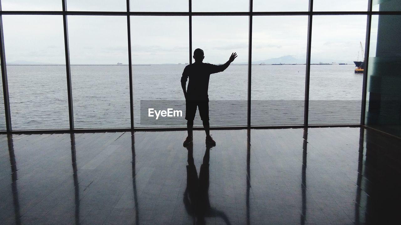 Silhouette Man Looking At Sea Through Window