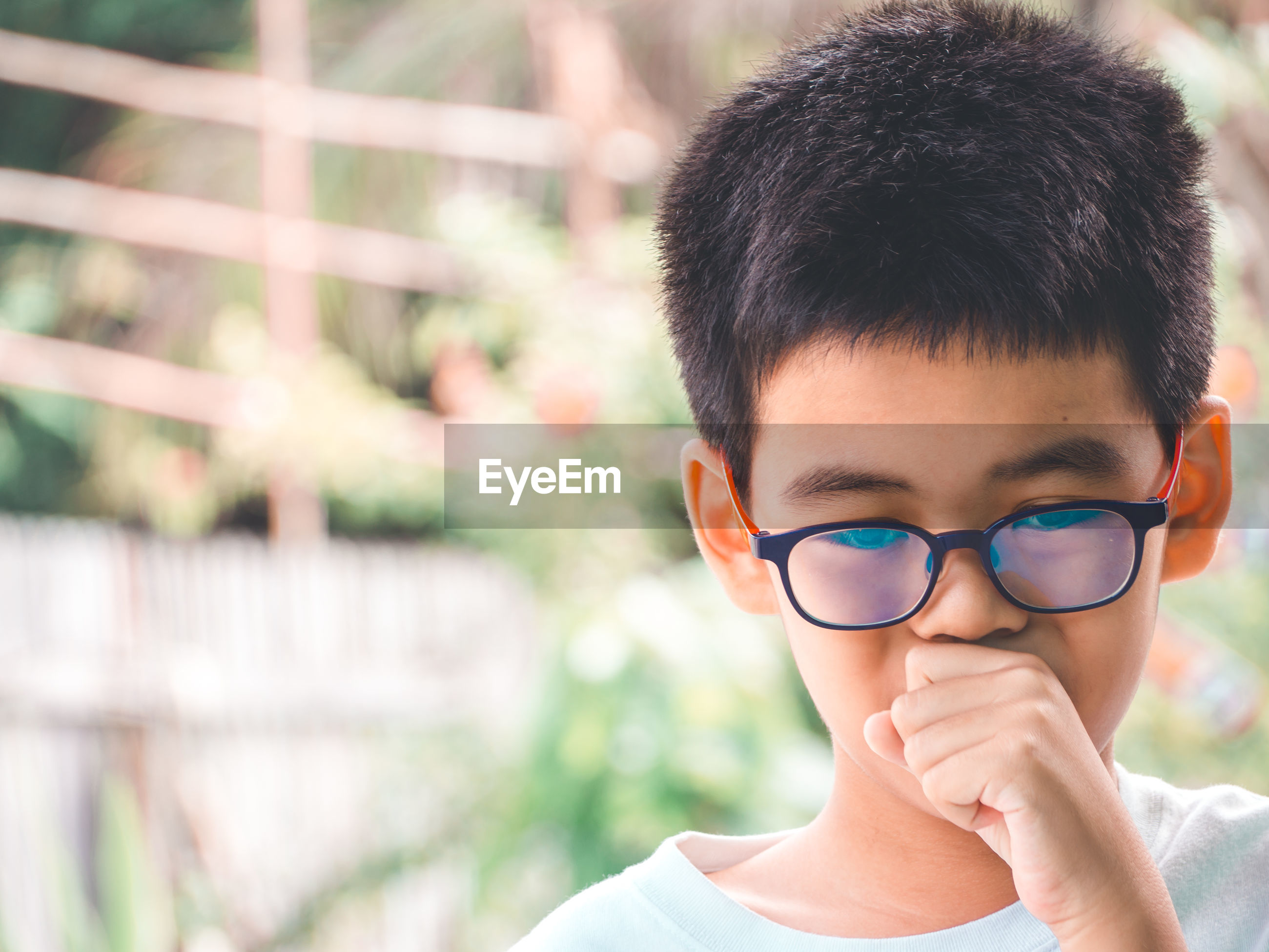 Close-up of boy with cold and flu outdoors