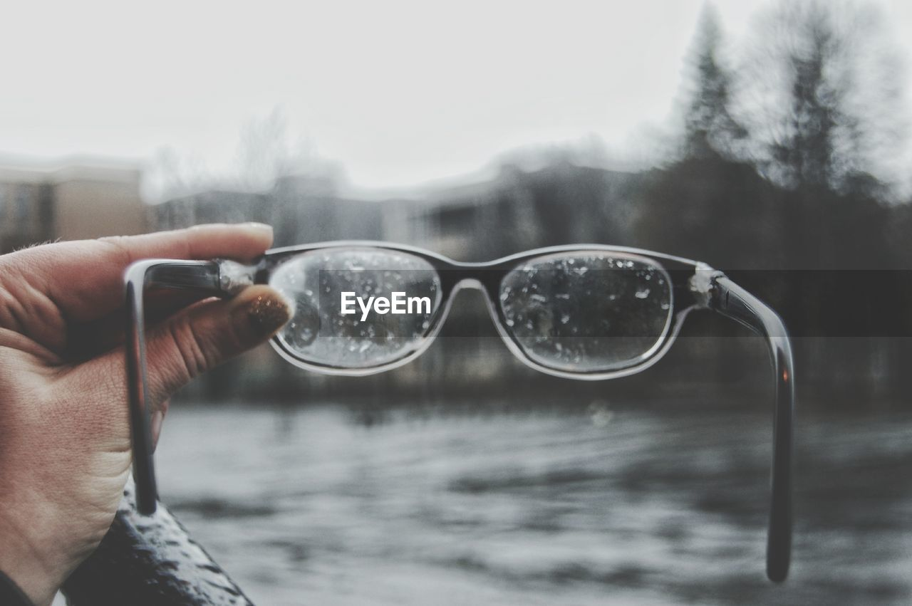 Close-Up Of Hand Holding Wet Eyeglasses By Lake