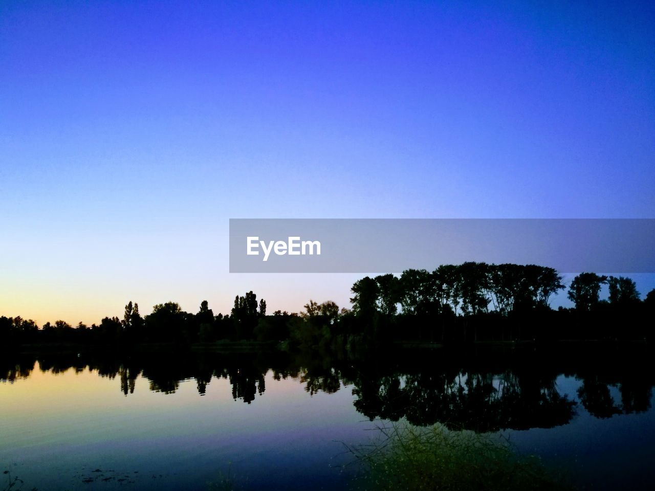 reflection, tree, silhouette, water, tranquil scene, beauty in nature, lake, nature, scenics, sky, tranquility, clear sky, outdoors, waterfront, sunset, no people, blue, day