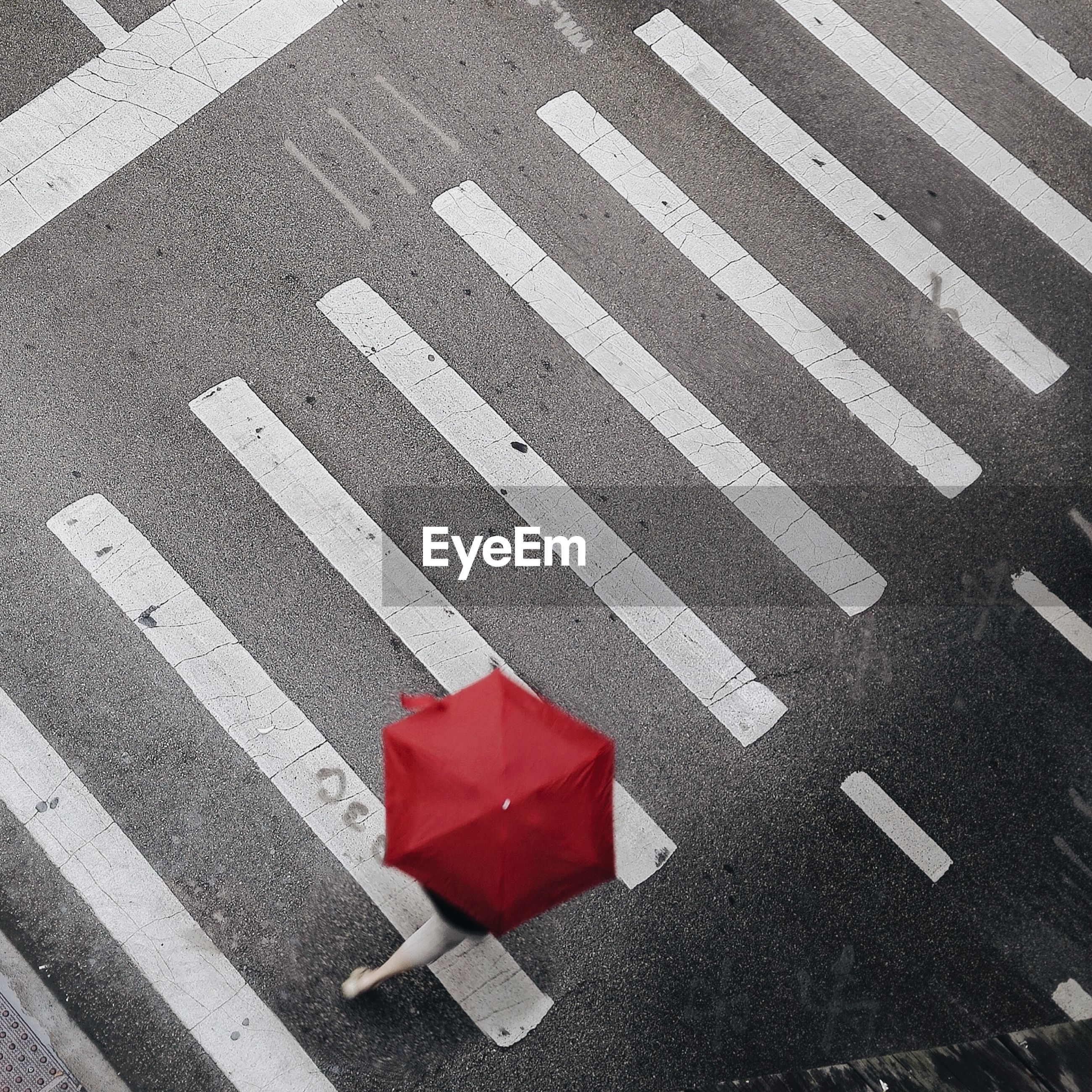 High angle view of person with red umbrella walking on zebra crossing