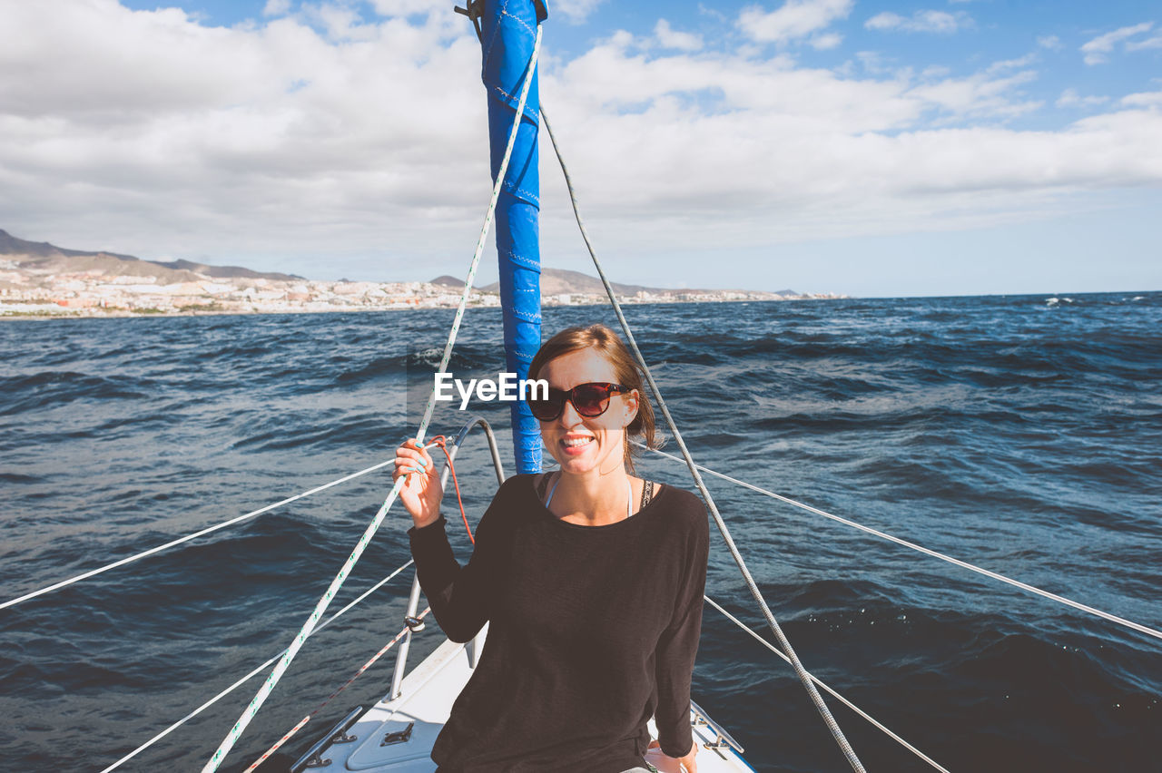 Portrait of smiling woman in sailboat against sky