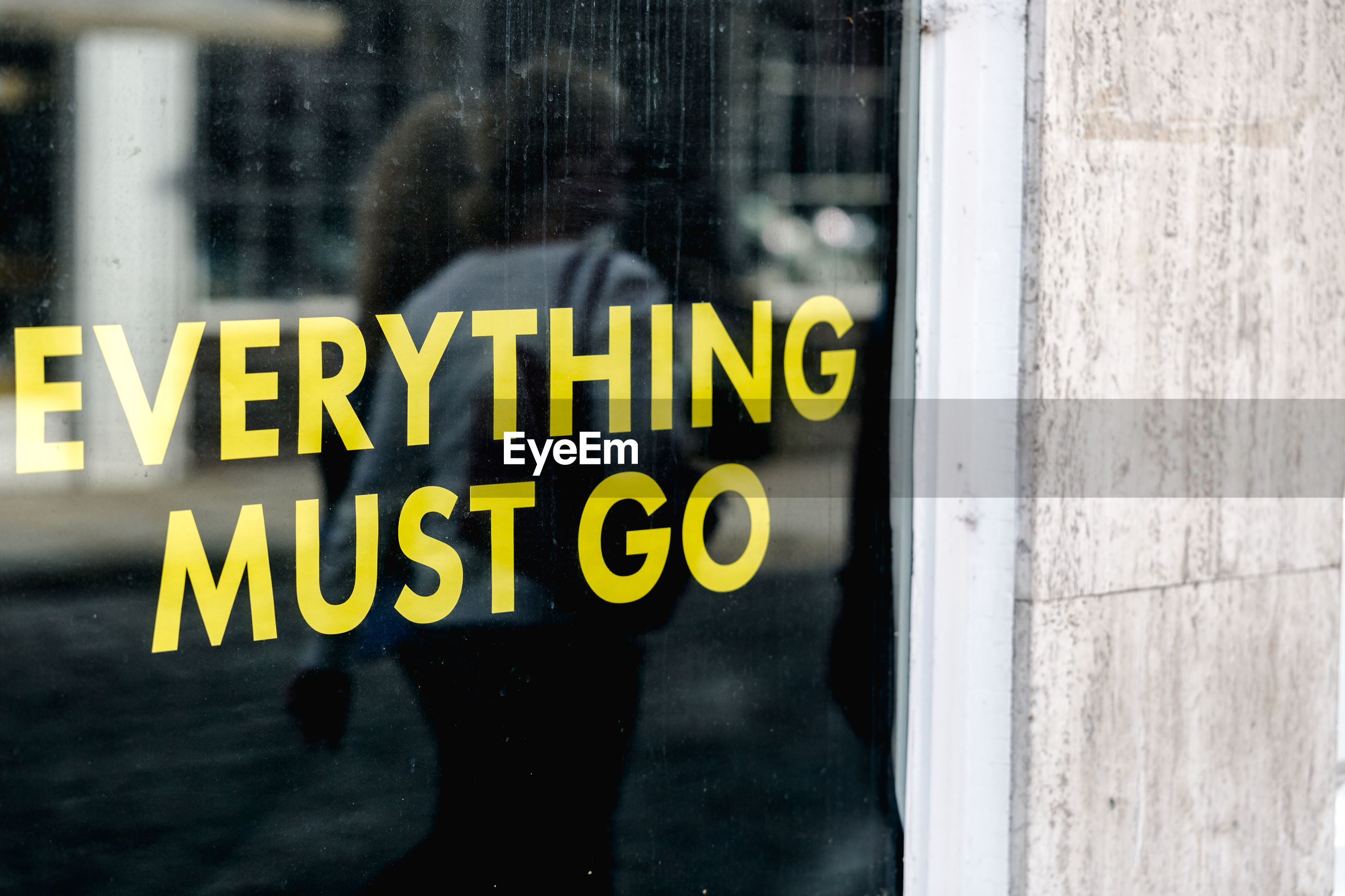 CLOSE-UP OF YELLOW SIGN ON WINDOW