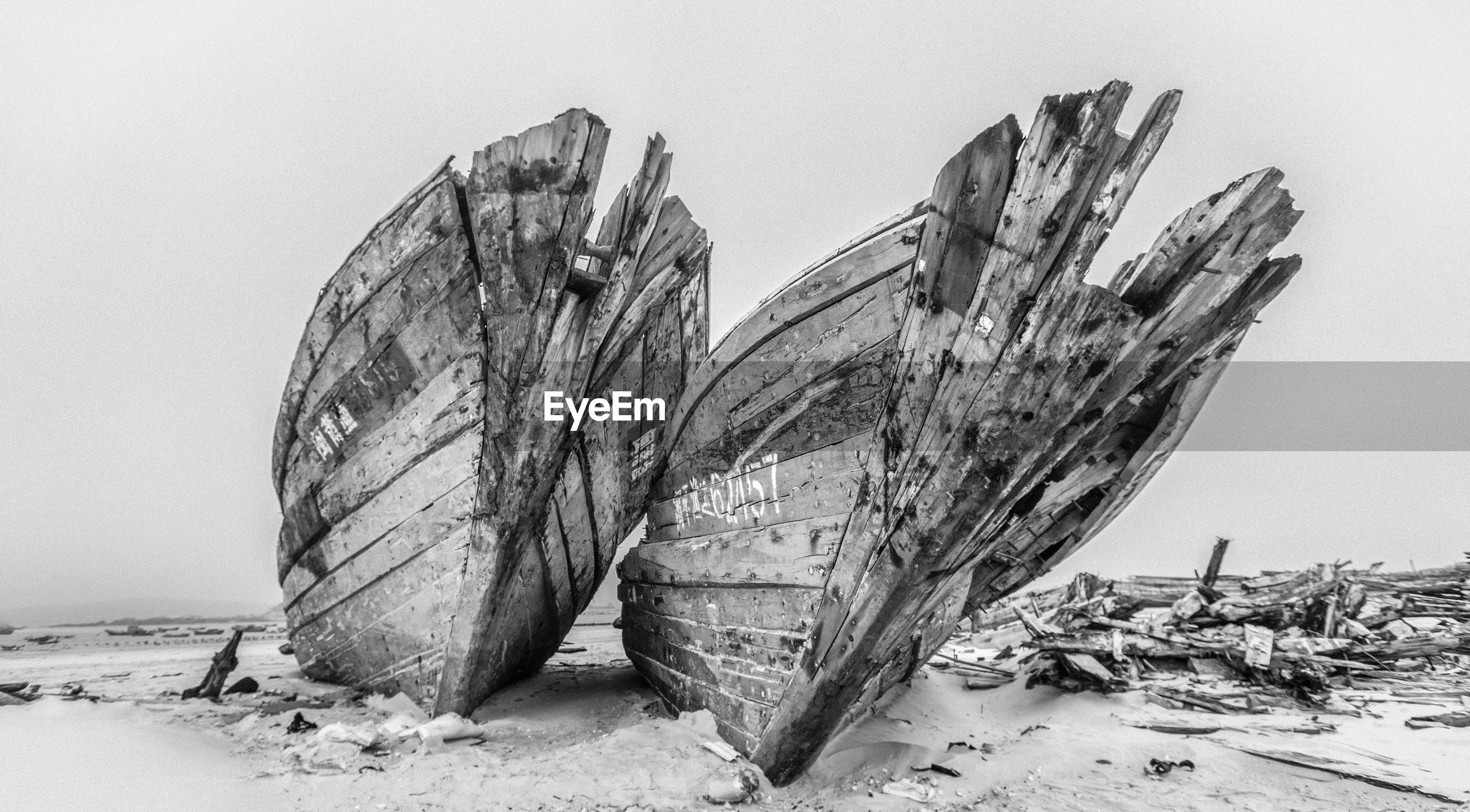 Low angle view of abandoned boats on beach against clear sky