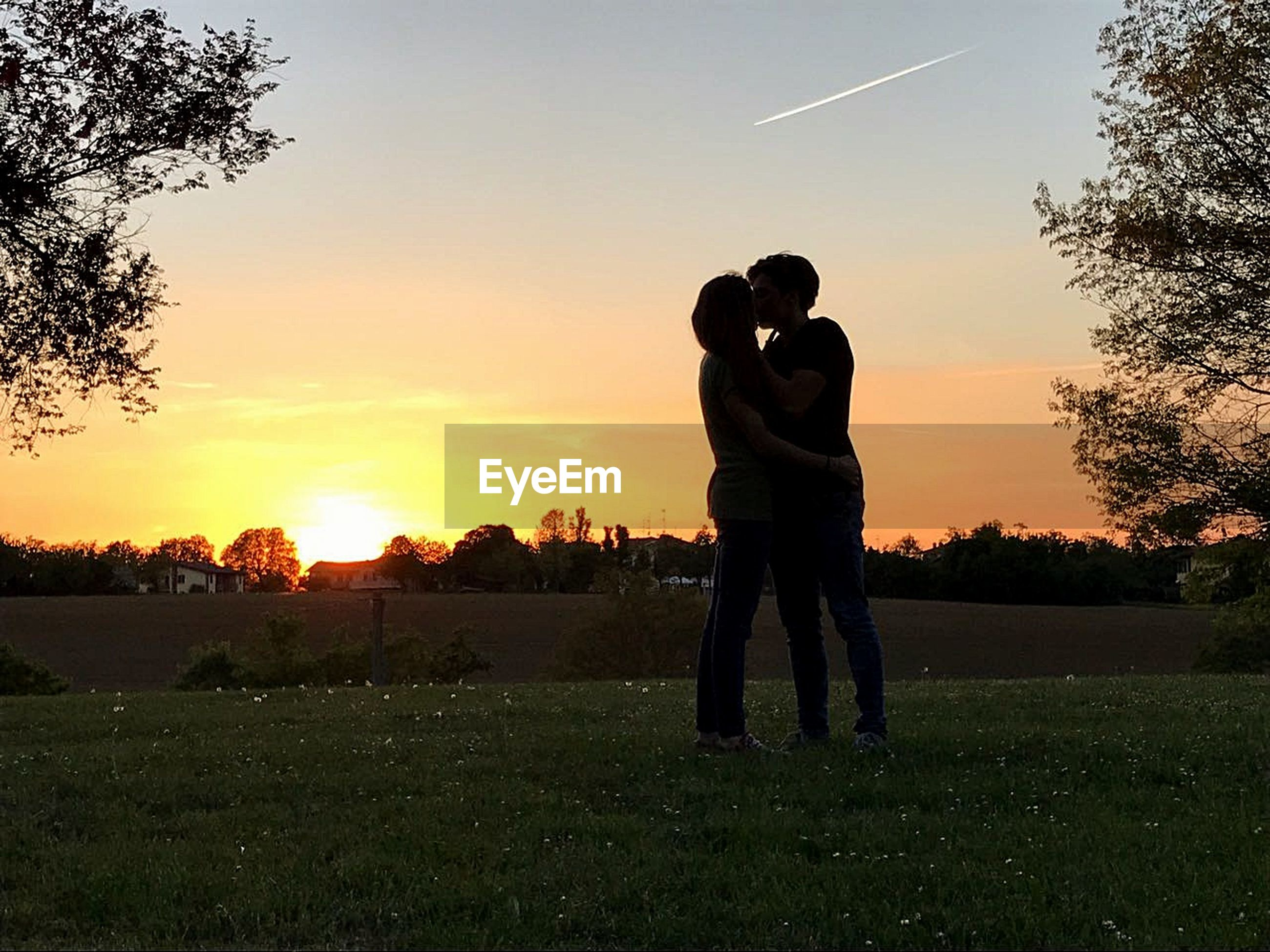 Full length couple kissing while standing on field against sky during sunset