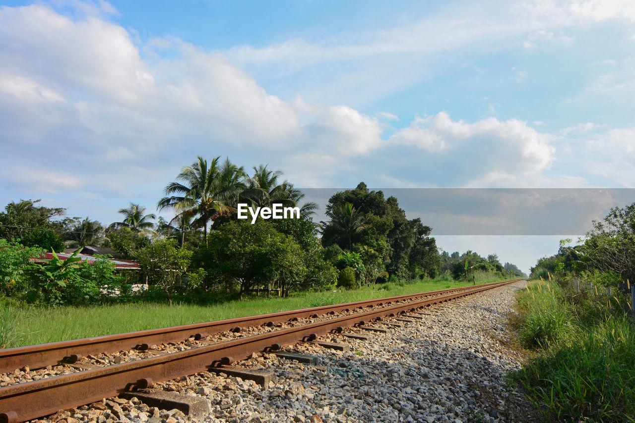 railroad track, sky, rail transportation, transportation, tree, cloud - sky, no people, nature, day, railroad, landscape, outdoors, blue sky, grass