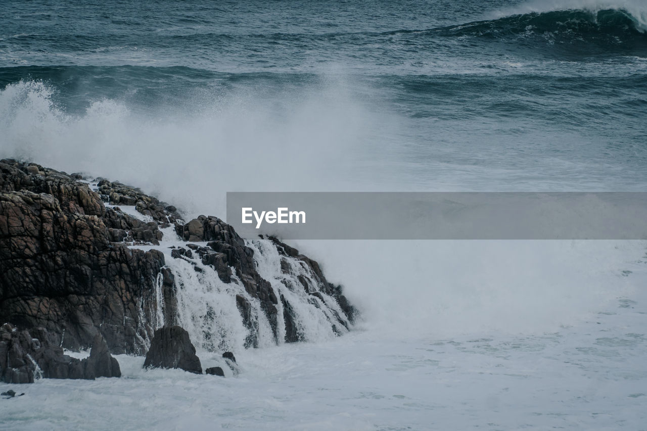 SCENIC VIEW OF WAVES BREAKING ON ROCKS AT SEA