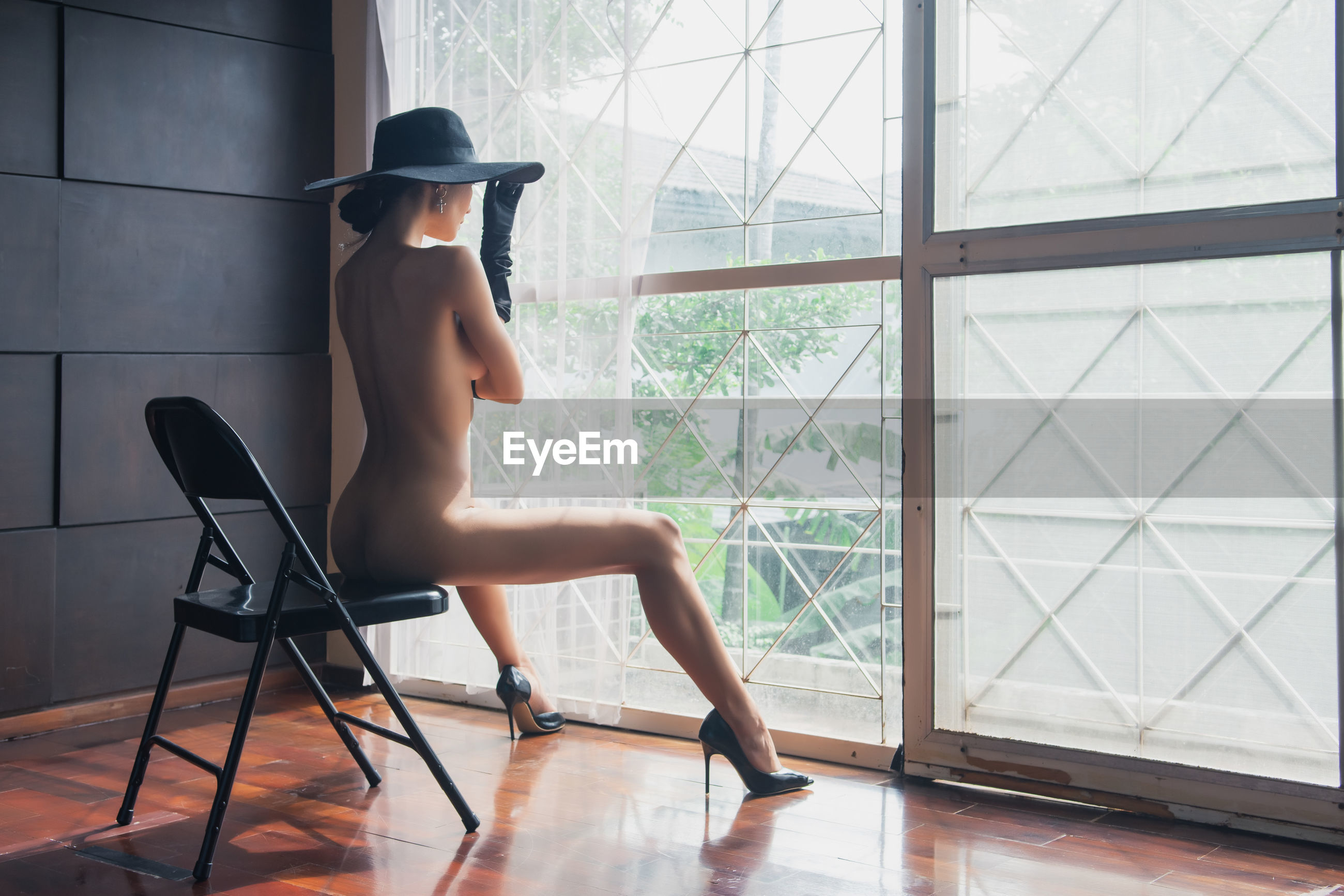 Naked woman sitting on chair by curtain against wall at home
