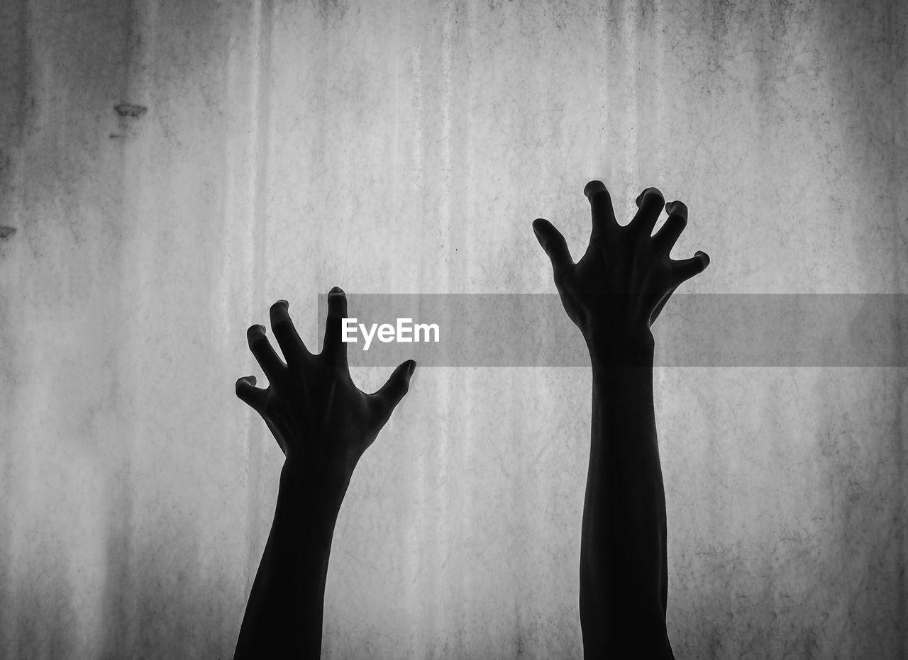 Silhouette man hand against sky
