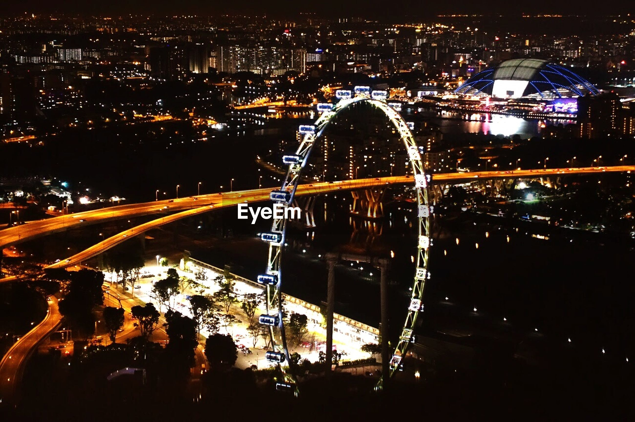 High angle view of illuminated singapore flyer and residential district