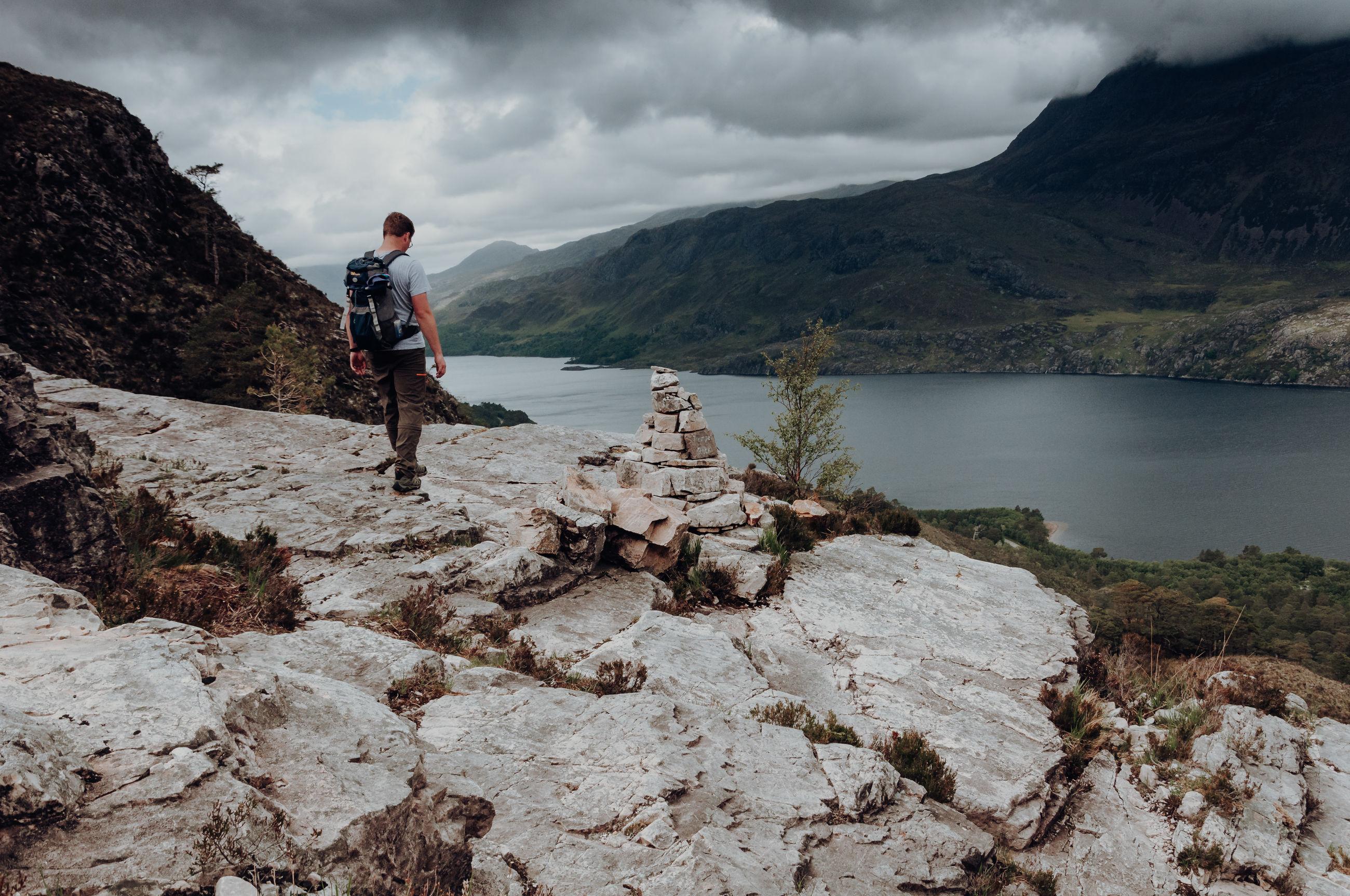 FULL LENGTH OF MAN STANDING ON ROCKS AGAINST MOUNTAIN