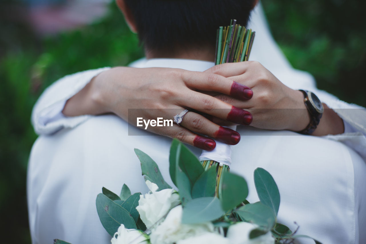 Cropped Hands Of Bride Holding Bouquet While Embracing Bridegroom