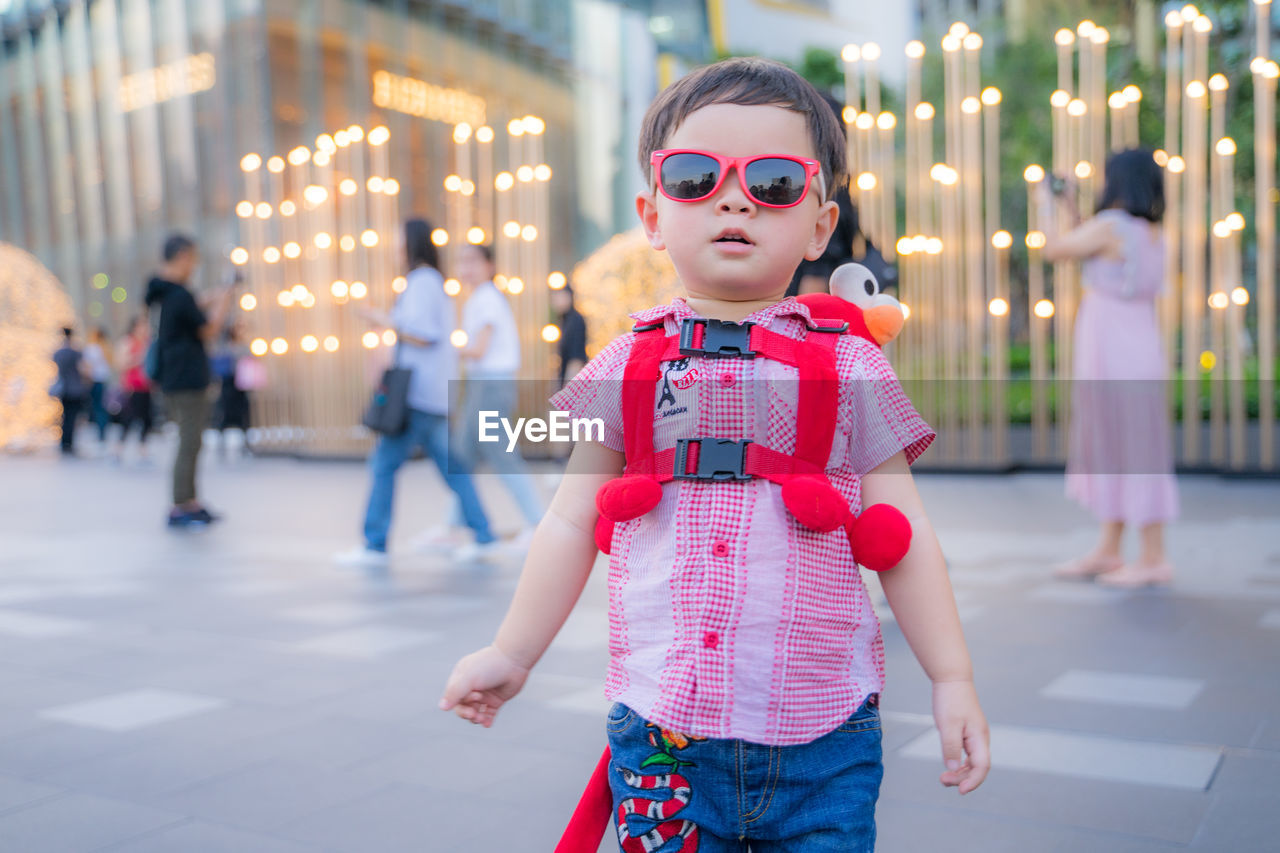 childhood, real people, focus on foreground, child, incidental people, one person, lifestyles, standing, innocence, women, men, boys, front view, casual clothing, females, girls, leisure activity, males, three quarter length, fashion, outdoors