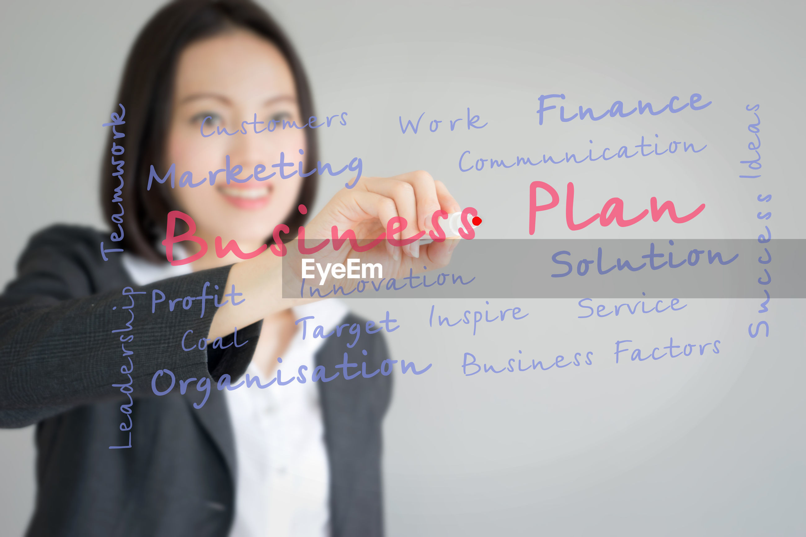 Digital composite image of businesswoman writing while standing against gray background