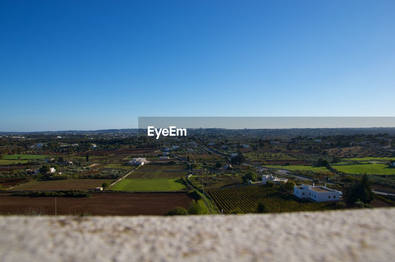 copy space, landscape, agriculture, field, clear sky, architecture, day, nature, town, rural scene, outdoors, tranquil scene, blue, no people, scenics, beauty in nature, high angle view, built structure, patchwork landscape, tranquility, building exterior, sky